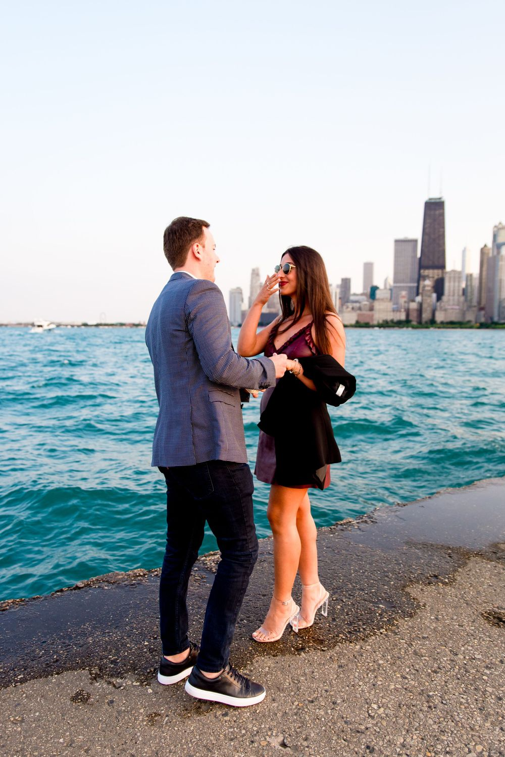 young woman smiling at fiance in front of Chicago skyline after North Avenue Beach proposal