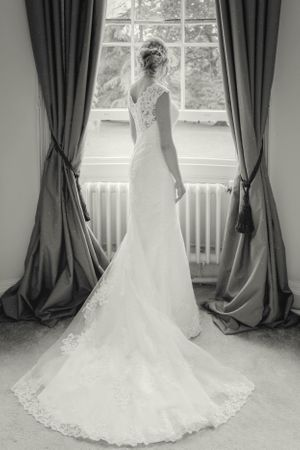 Bride looking out of window at Eastington Park, Gloucestershire