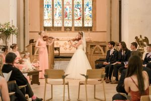 Bride playing violin at her wedding, Minchinhampton