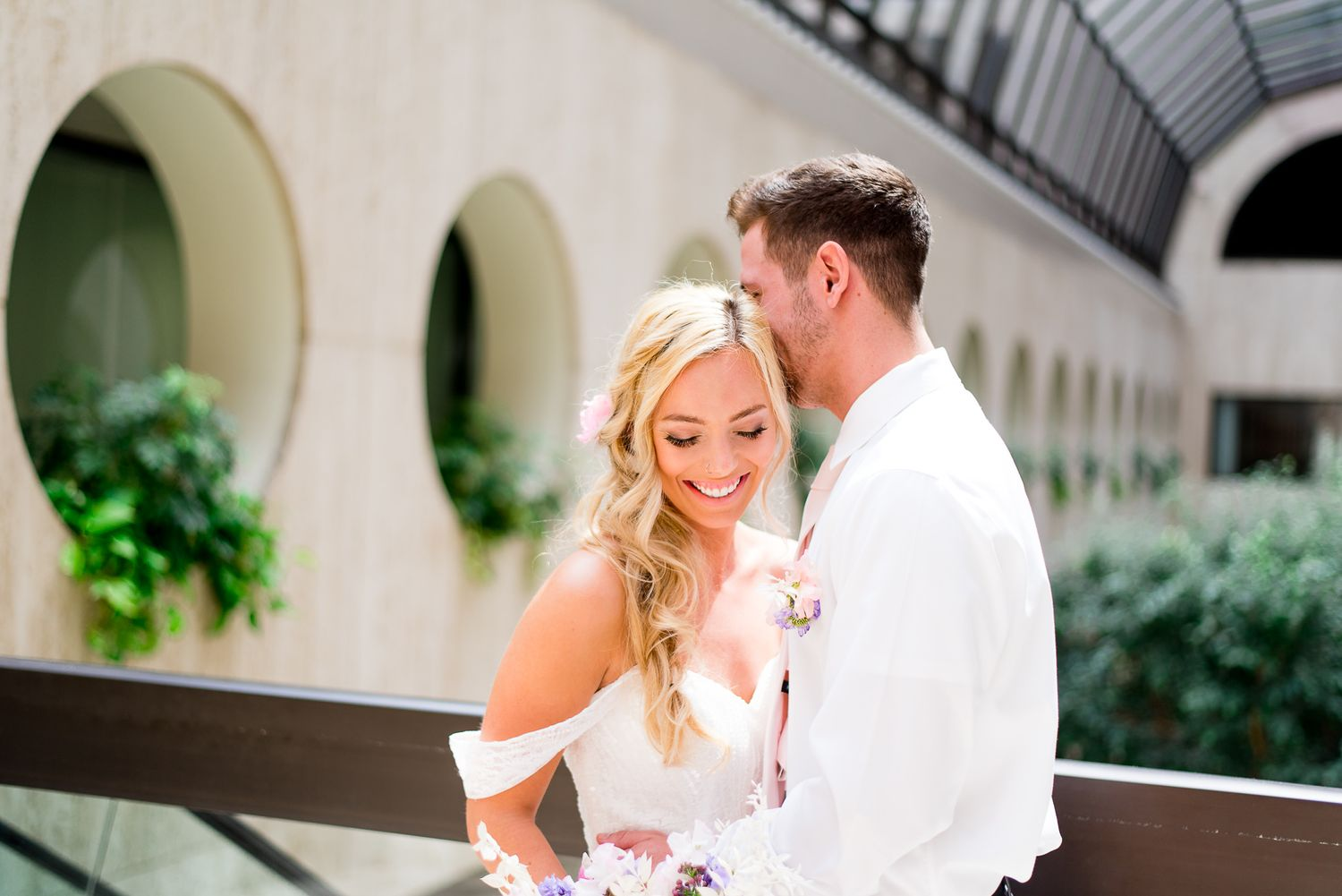 blonde bride smiling and laughing while groom whispers to her at The Center Cincinnati