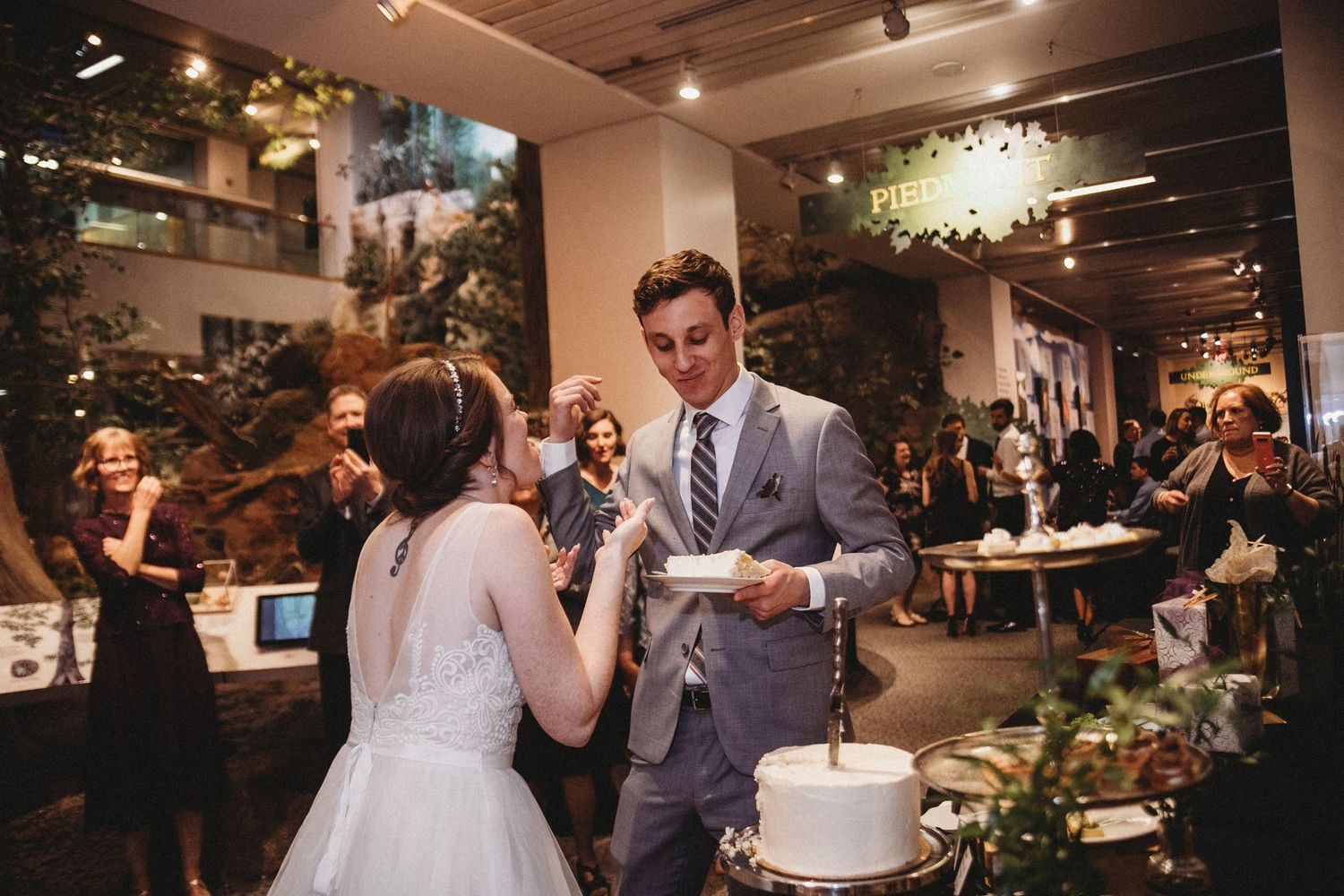 bride and groom feed rocky top catering cake to each other in front of family and friends