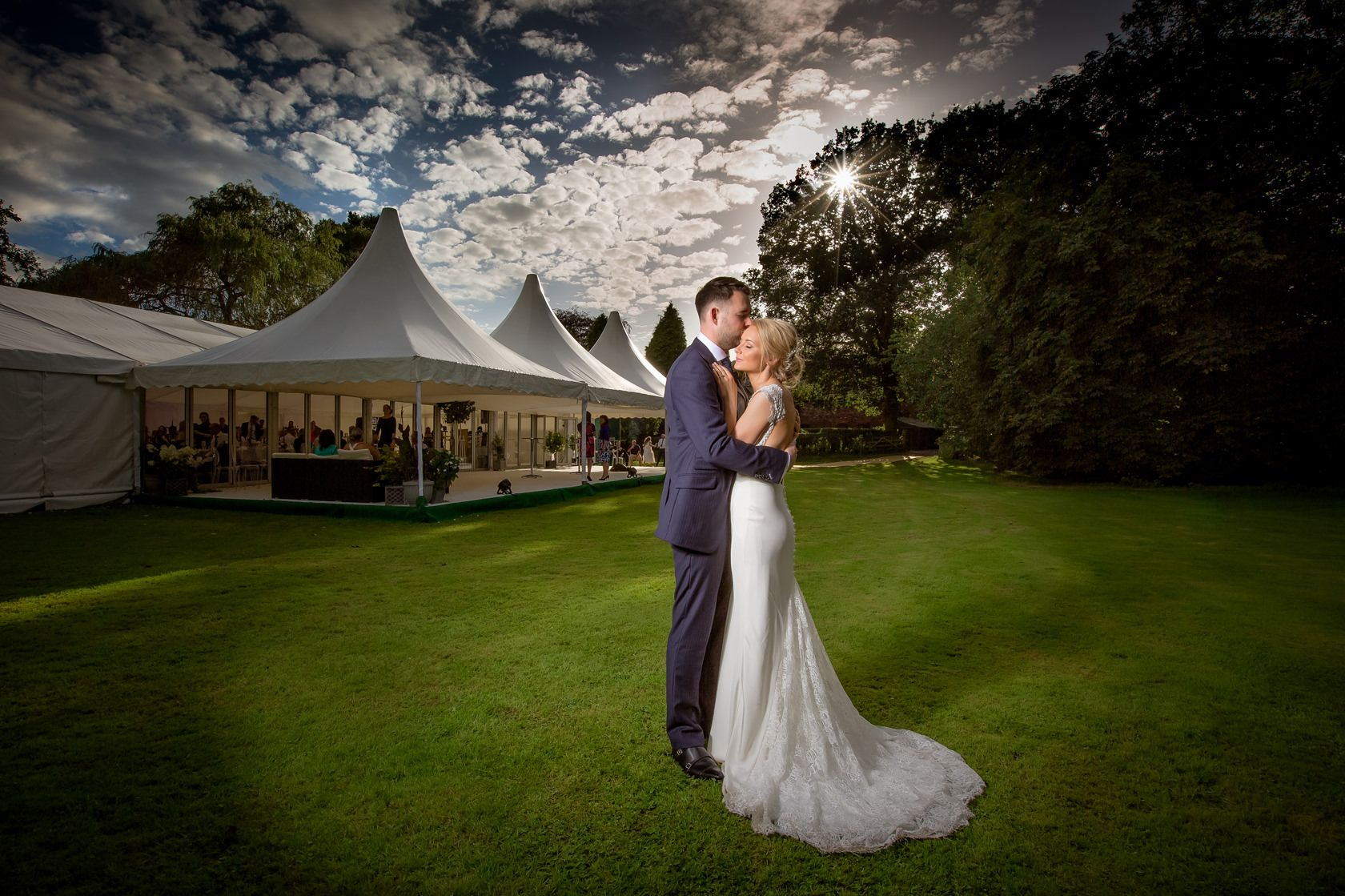 A groom holds his beautiful bride closely during sunset at their outdoor Marquee wedding in Peover Cheshire