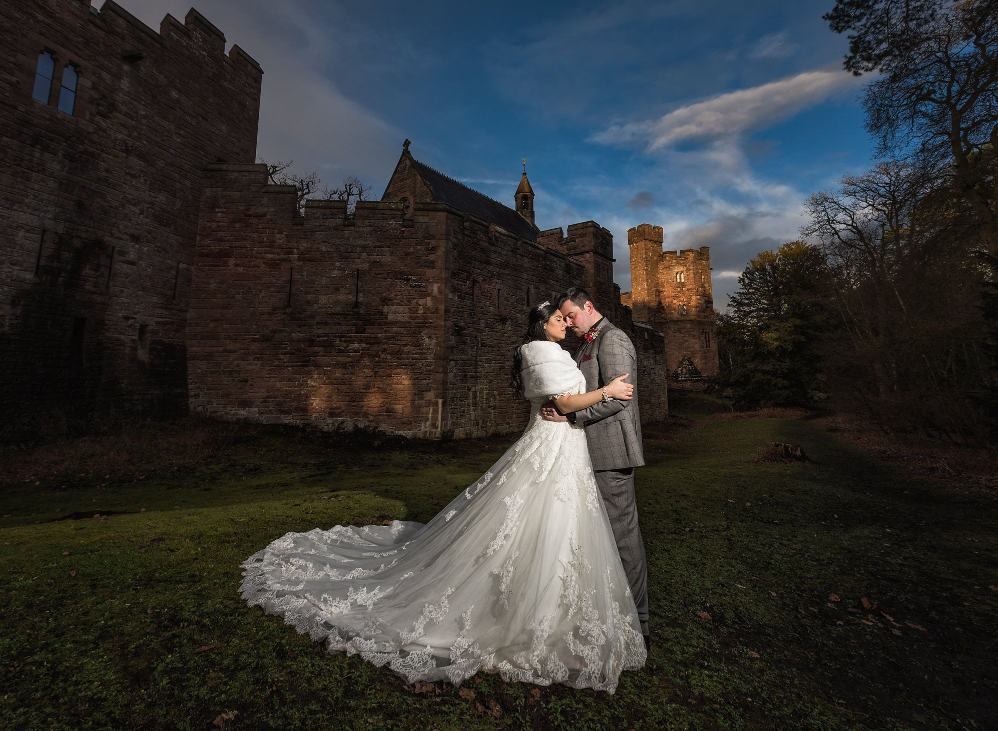 Bride and groom hold each other outside the walls of Peckforton Castle on their summer wedding day in Cheshire