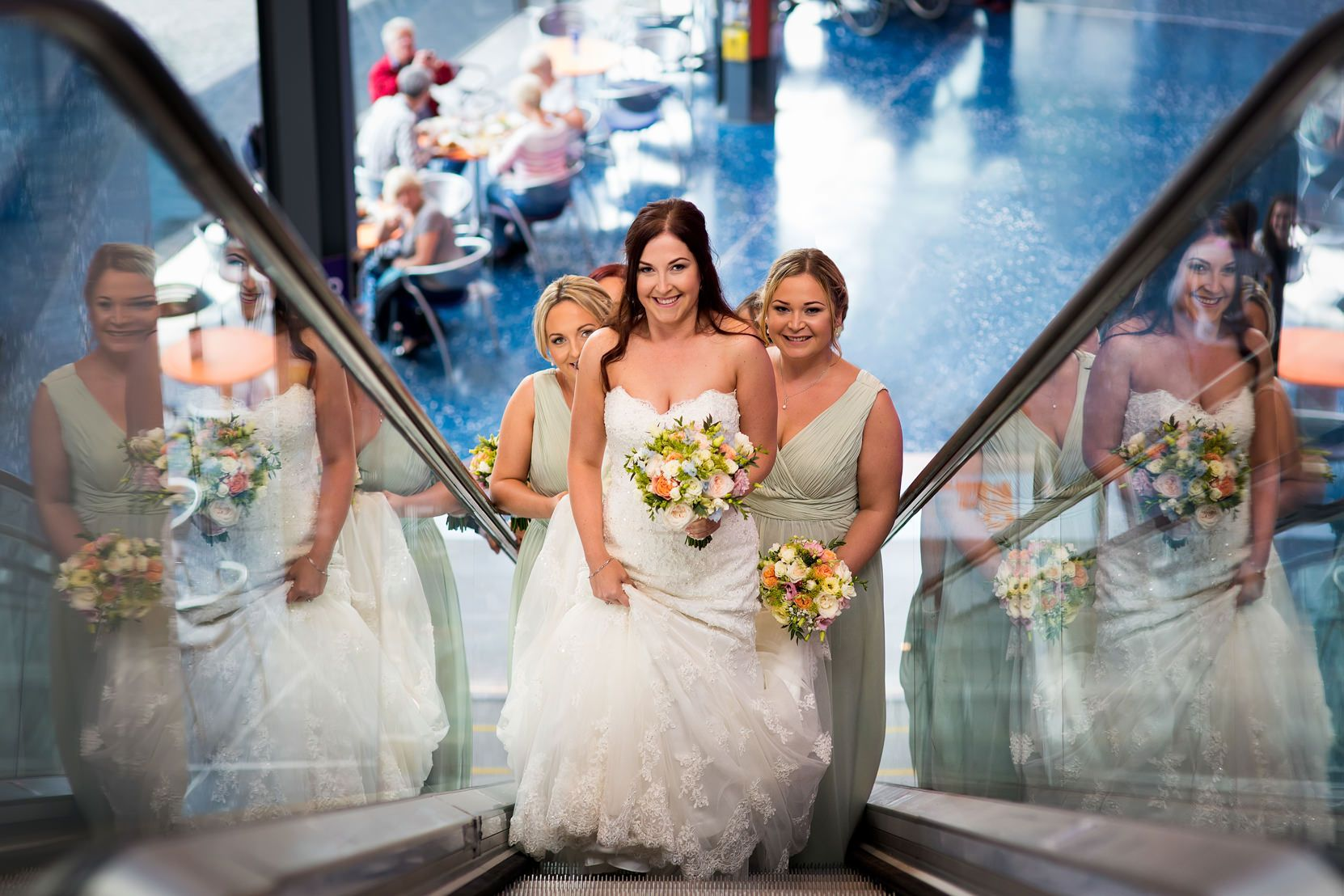 A bride in white dress travels up the escalator on her wedding day at The Lowry in Manchester with her bridesmaids