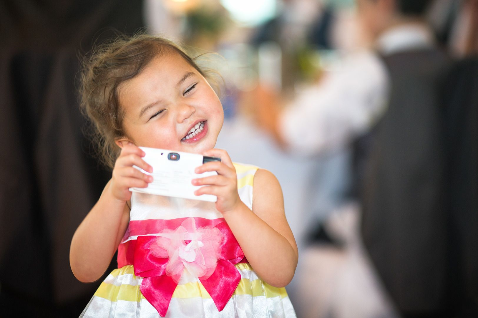A little oriental girl takes a photo with her small camera at a wedding inside The Lowry venue in Manchester