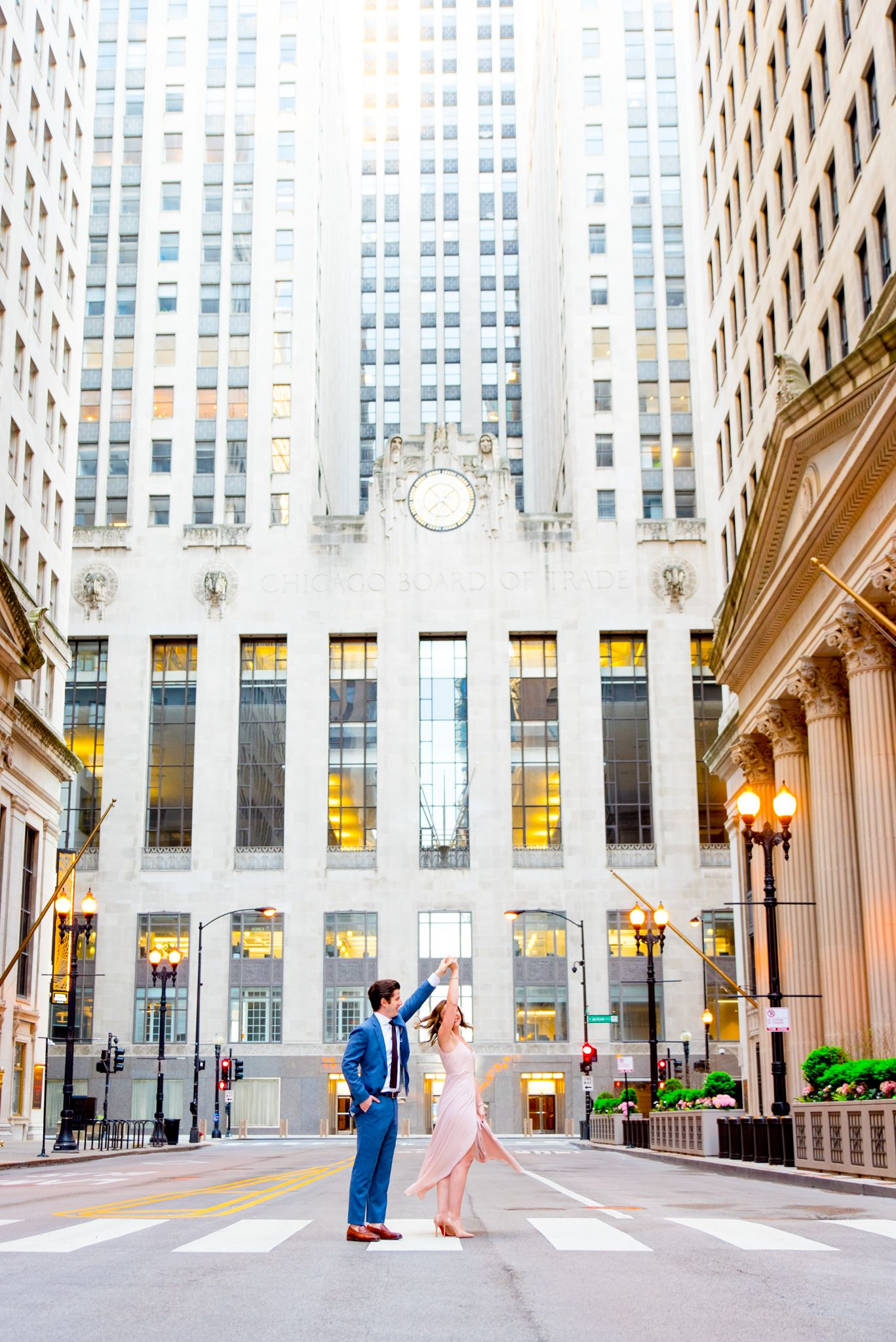 man and woman spin around in the empty street in front of Chicago Board of Trade for engagement pictures