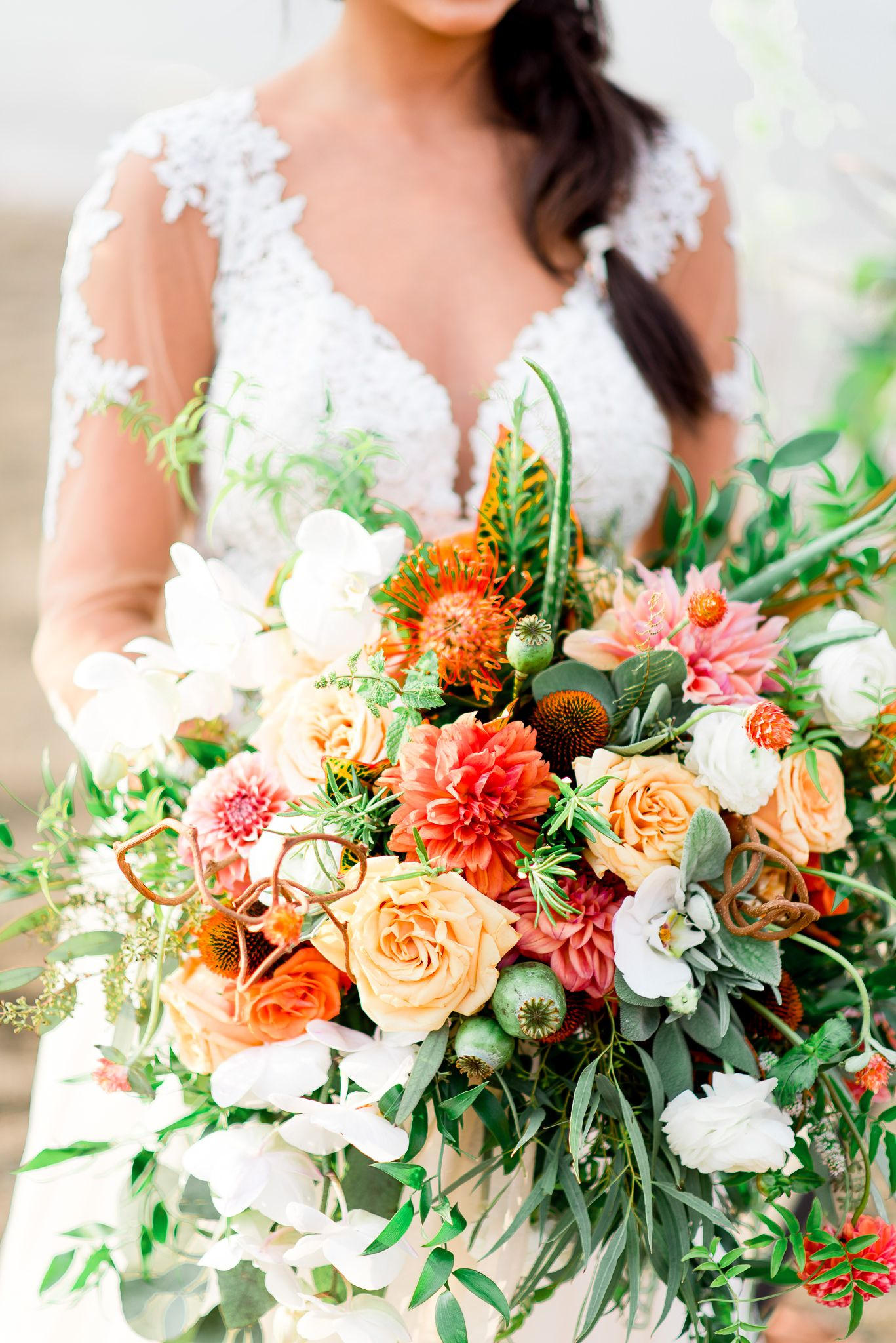 orange fall wedding bouquet with orchids, croton, dahlias, roses, lamb's ear, and aloe for a beach elopement in Chicago