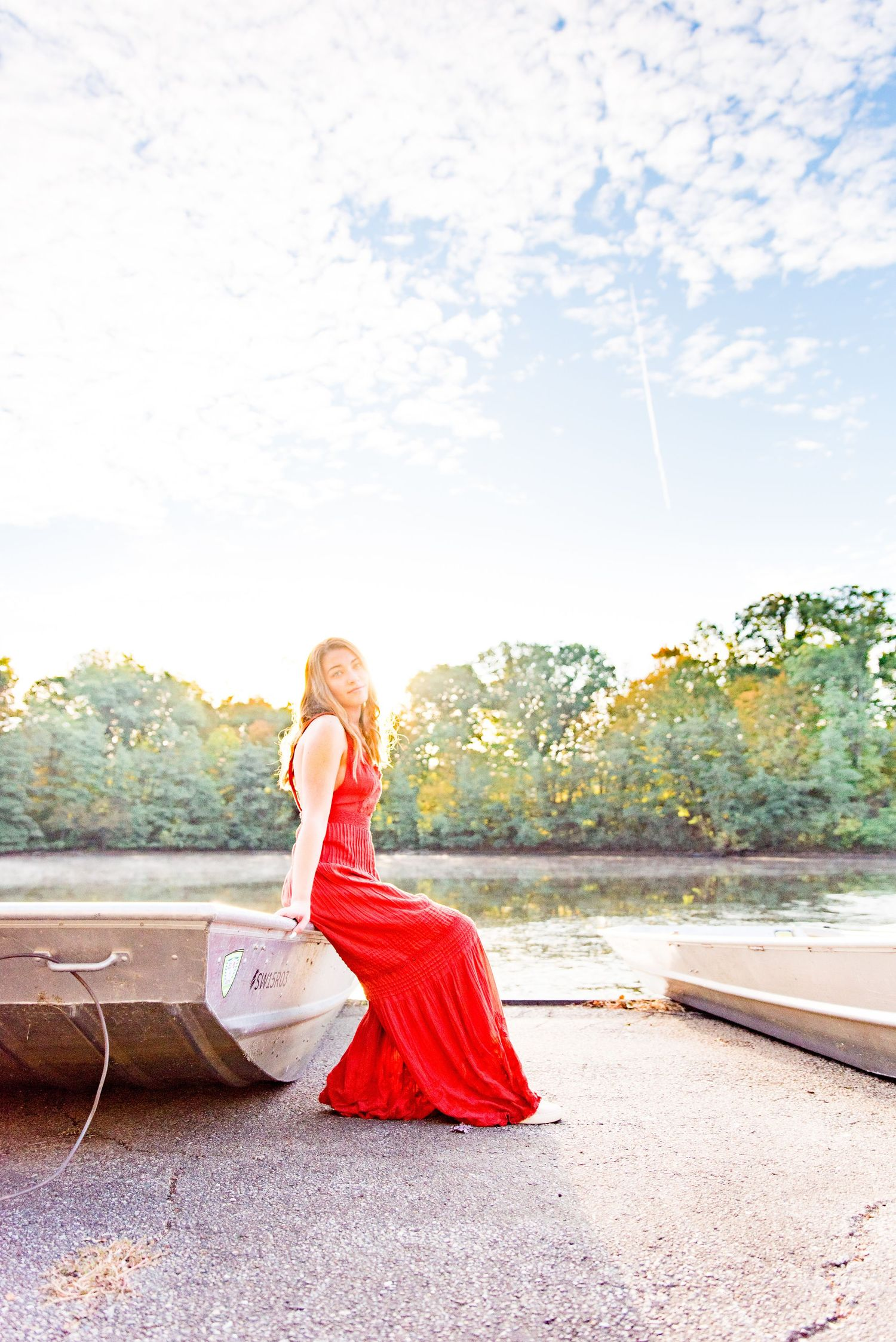 young woman in red jumpsuit sits on edge of boat in front of a pond under a blue cloudy sky at Sharon Woods Park