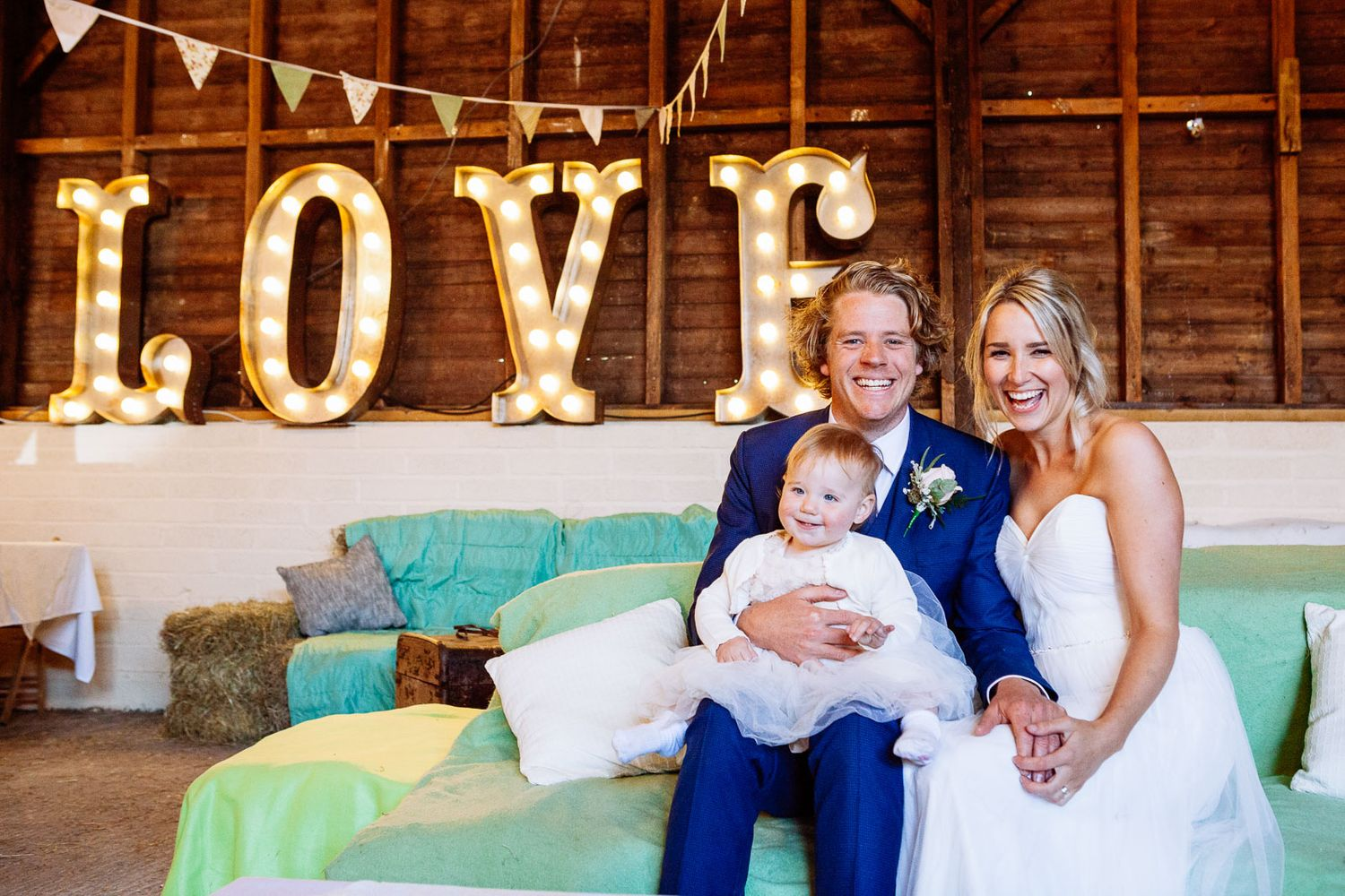 Bride and Groom with their daughter at natural rustic barn wedding in Devon