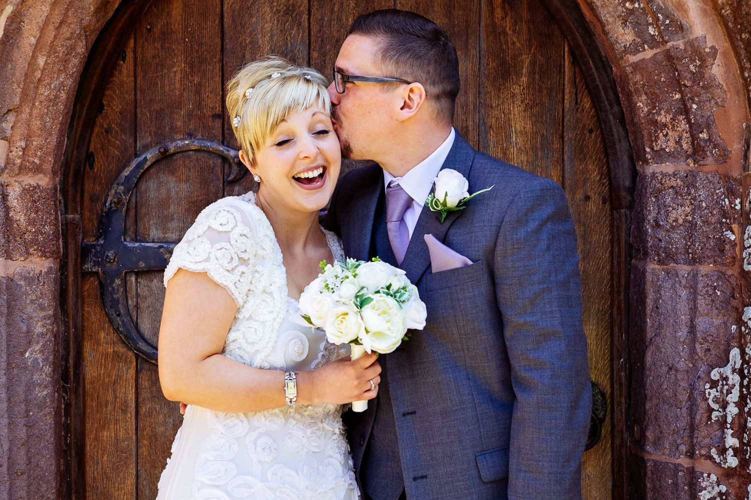groom kissing bride in front of church door after wedding by Devon wedding photographer
