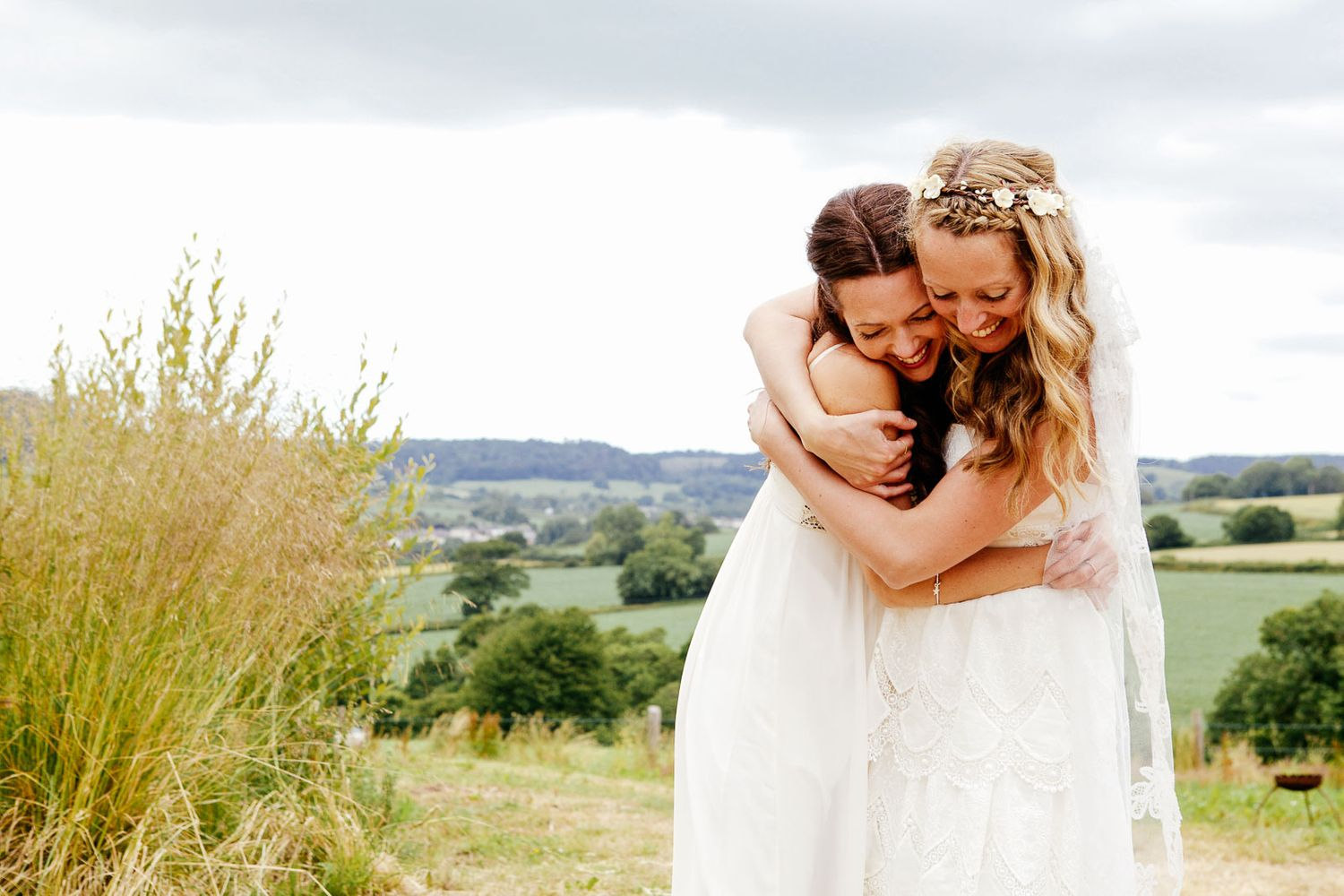 bride and sister embrace at a Devon festival wedding