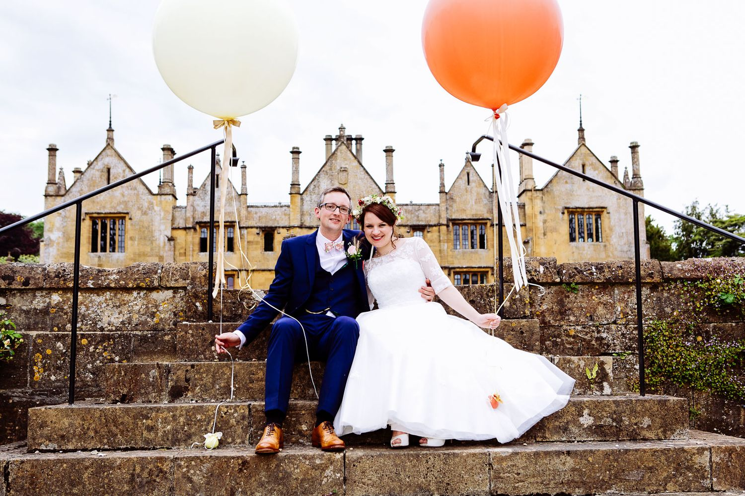 couple portraits at wedding in Dorset. couples hold large balloons in vintage style wedding