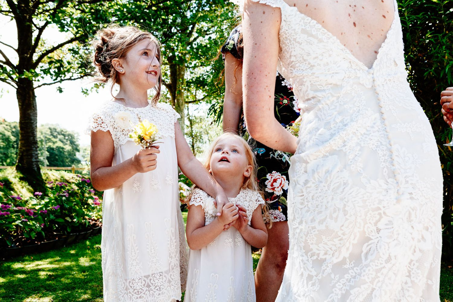 photography of flower girls looking up to bride by Tuscany based wedding photographer