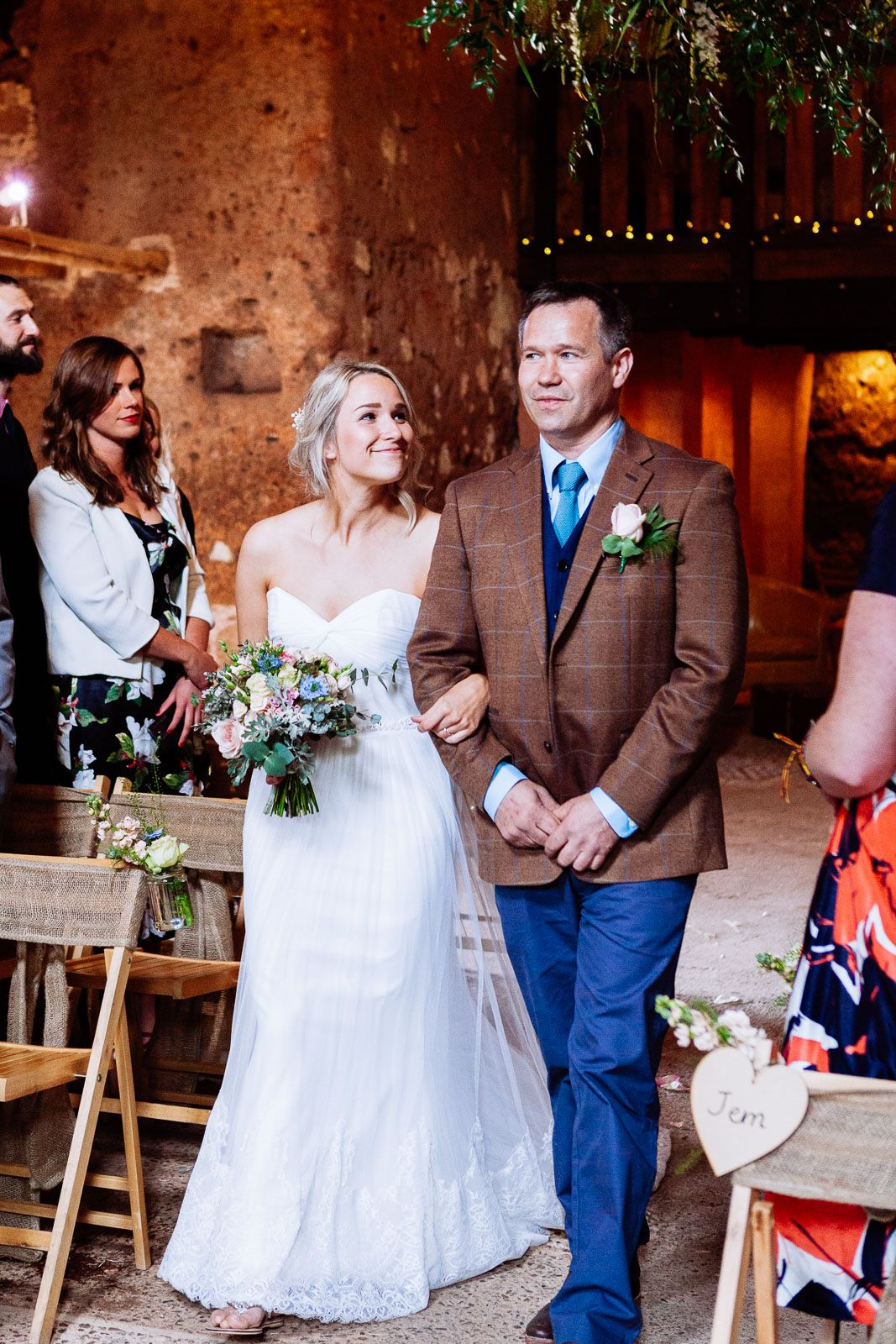 bride and after of the bride walking down the aisle in Exmouth Devon barn wedding