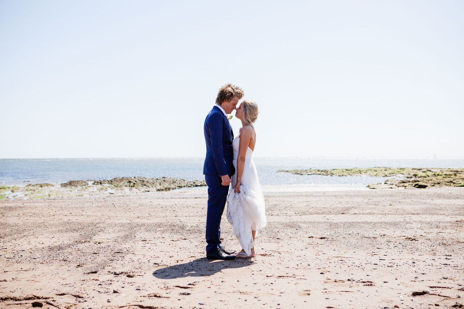 wedding couple on beach by by Tuscany based wedding photographer