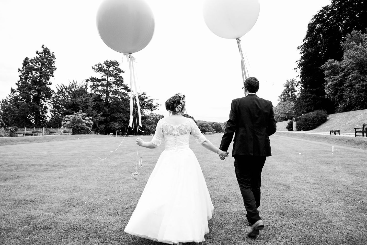 vintage style wedding couple holding hands and balloons