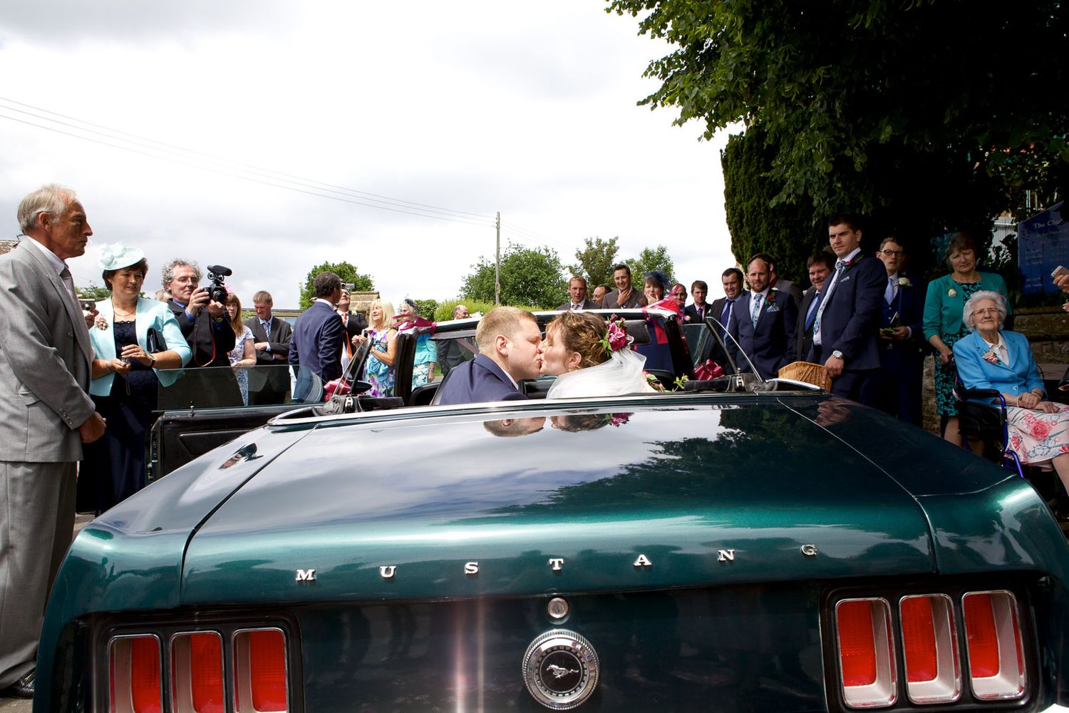 bride and groom kiss in the back of a vintage car at this wedding in Somerset