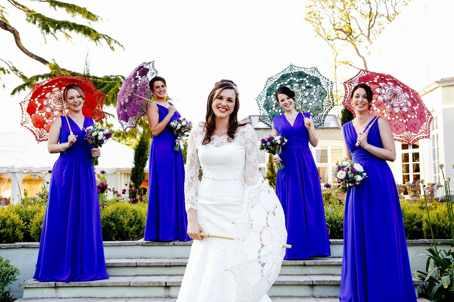 bridesmaids with colourful parasols by by Tuscany based wedding photographer