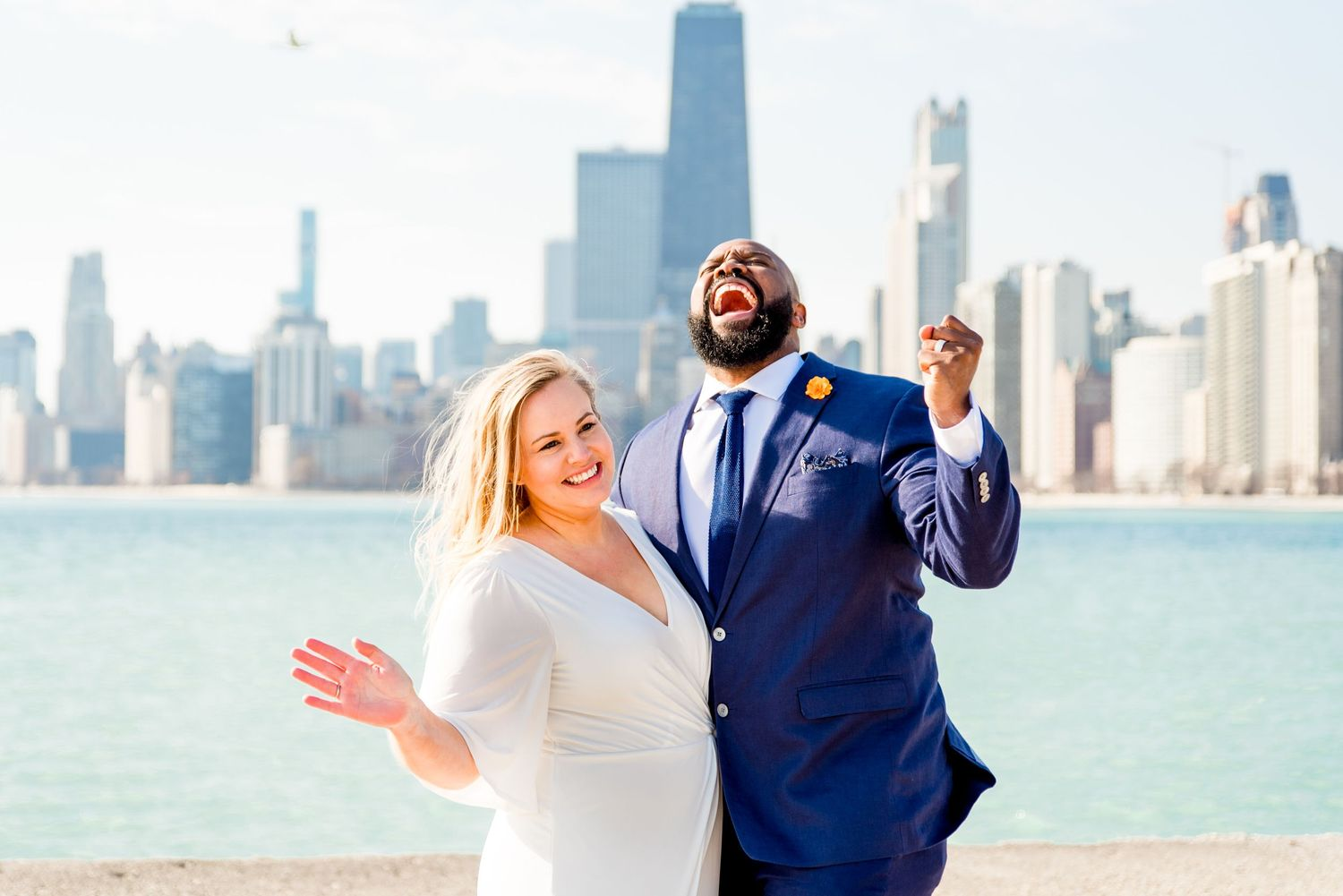 man and woman cheering on pier after north avenue beach elopement in chicago