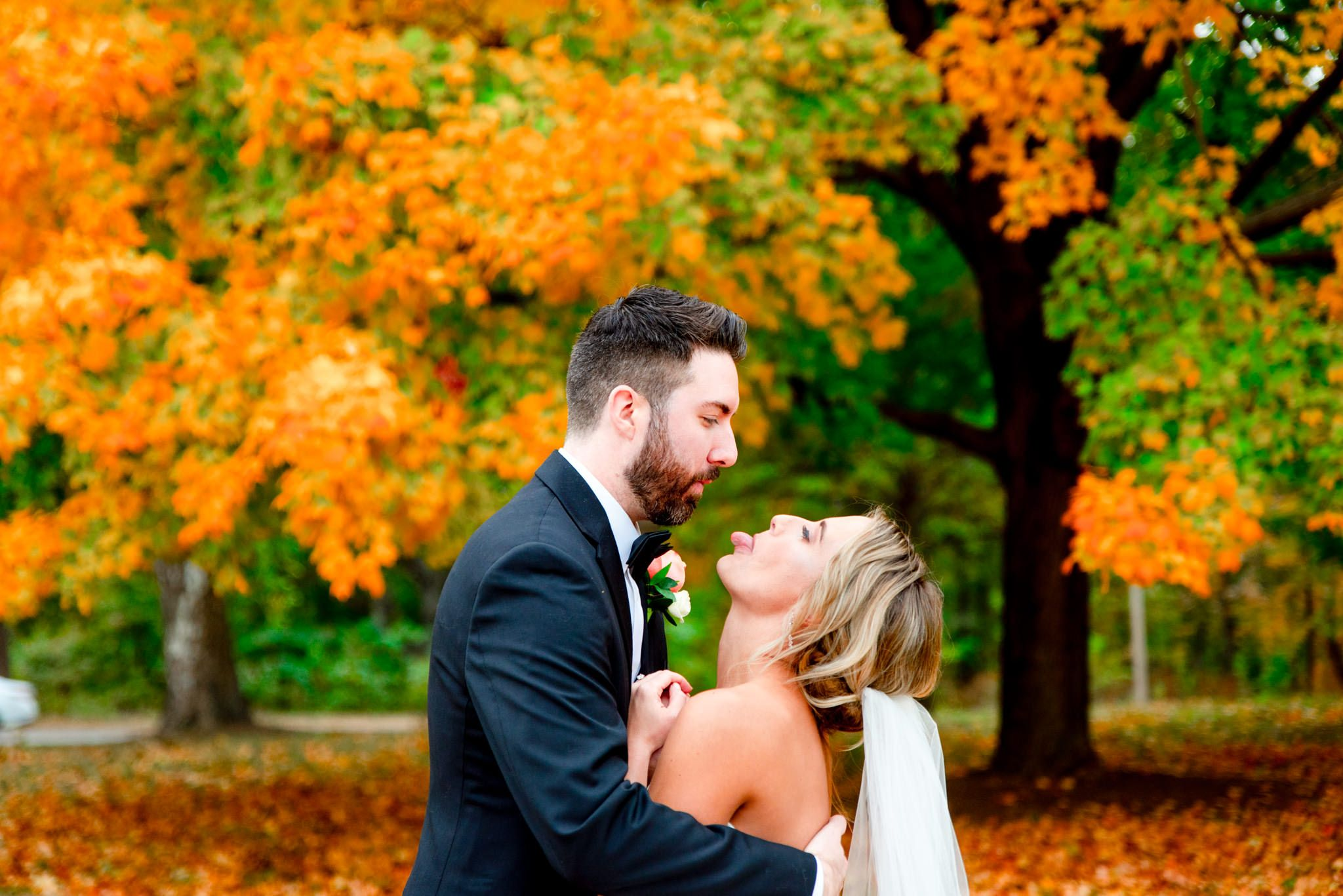 bride sticking tongue out at groom during fall wedding pictures in STL Forest Park