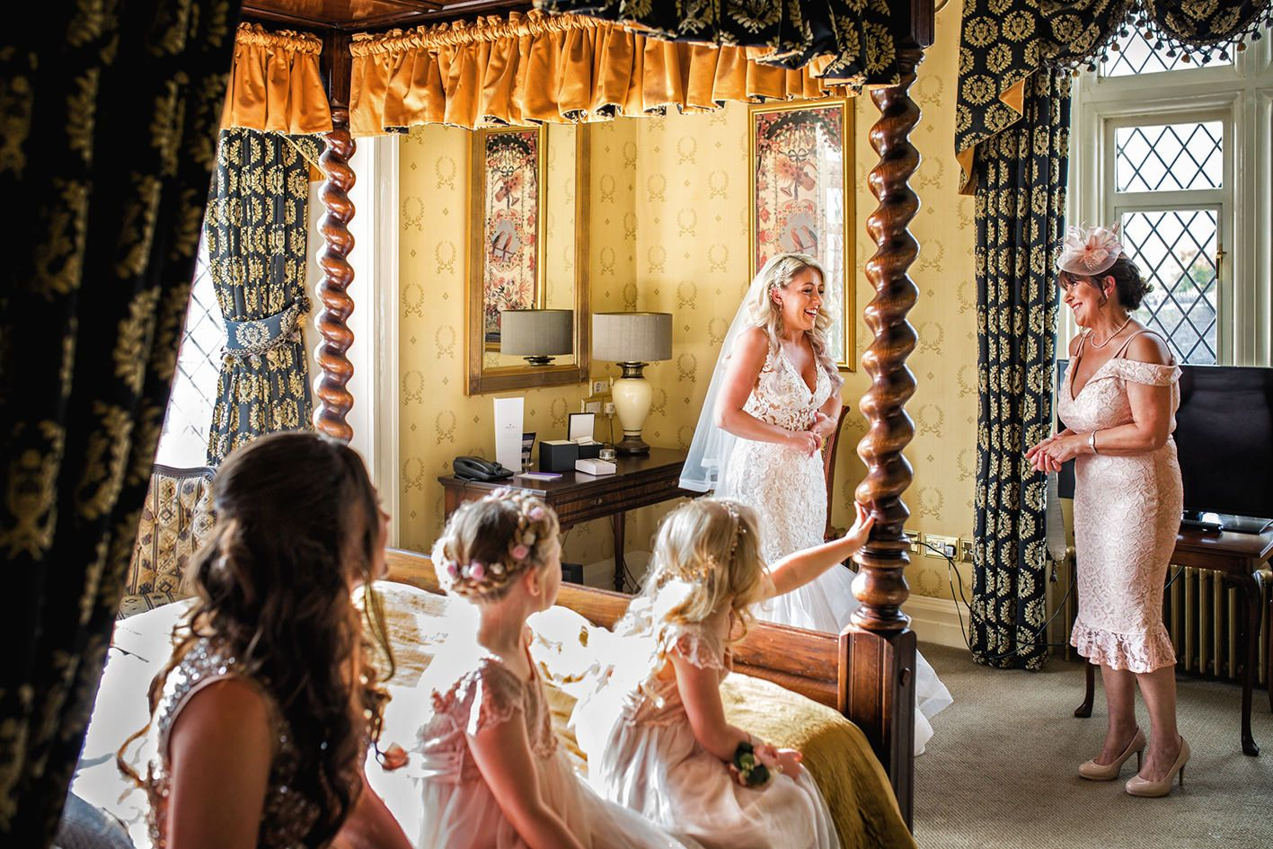 Bridesmaids and the brides mother admire her wedding dress in the bedroom of Crewe Hall wedding venue
