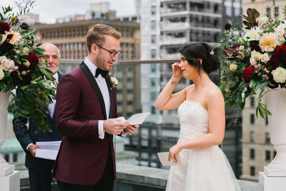 bride crying during groom reading vows with city scape behind them rooftop ceremony toronto