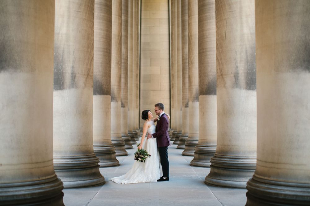 bride and groom hugging in between tall beige columns pittsburgh mellon