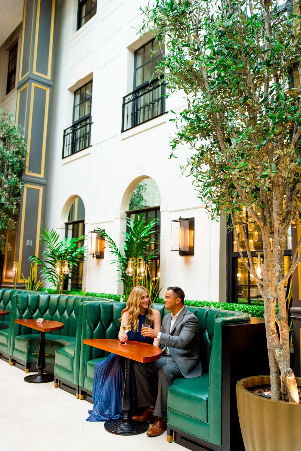 man and woman sit in green booth at Lytle Park Hotel for their engagement pictures