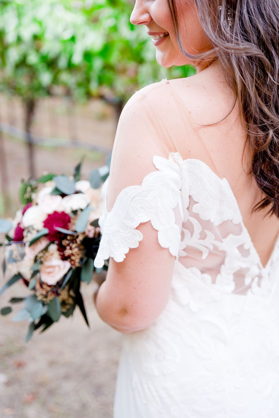 bride's lace wedding sleeve and red wedding flowers