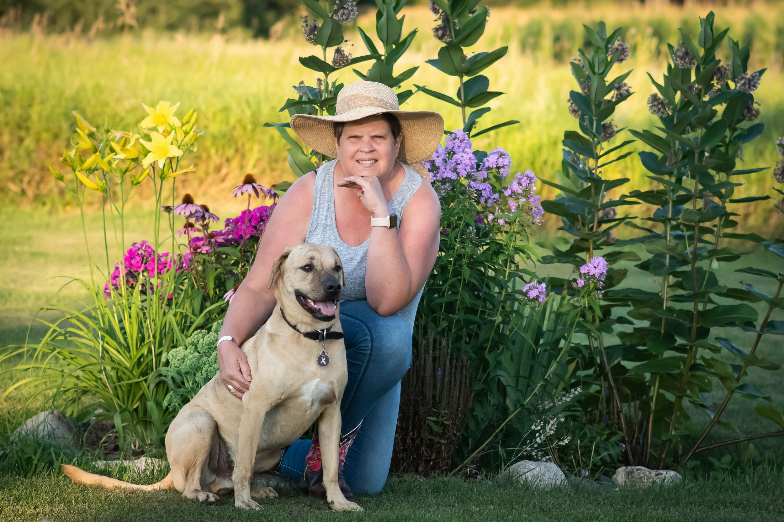 Photographer Myra J Horner kneeling in front of her flower garden with her beloved rescue pup Harley by her side.
