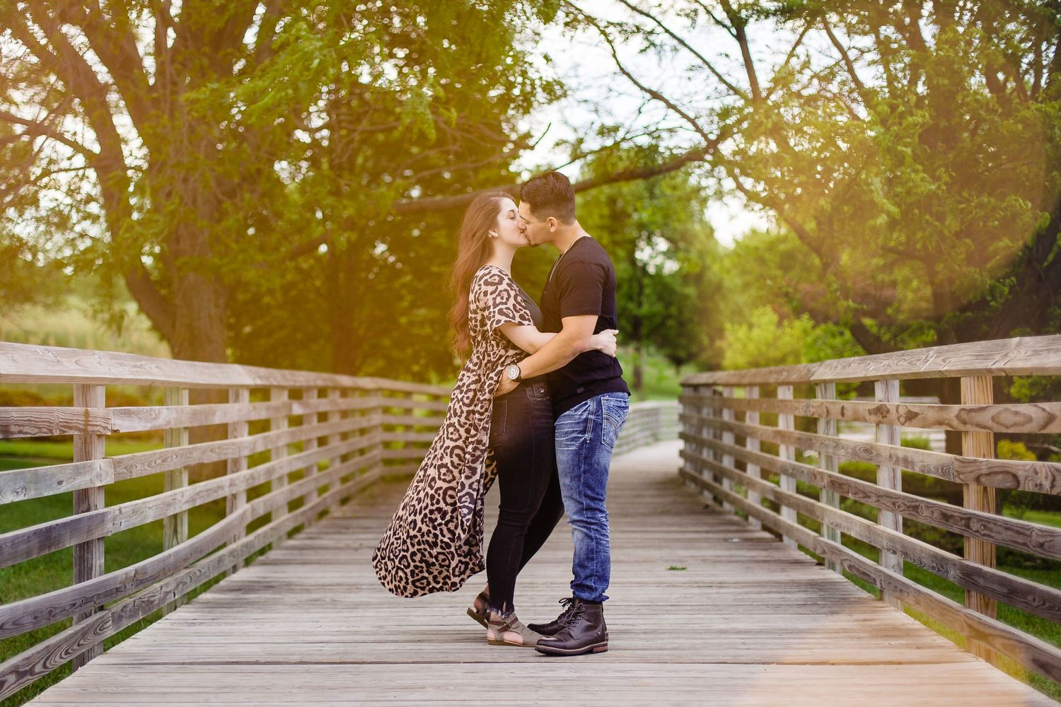 A couple kisses on a bridge between fairy lights at Mahoney State Park in Nebraska