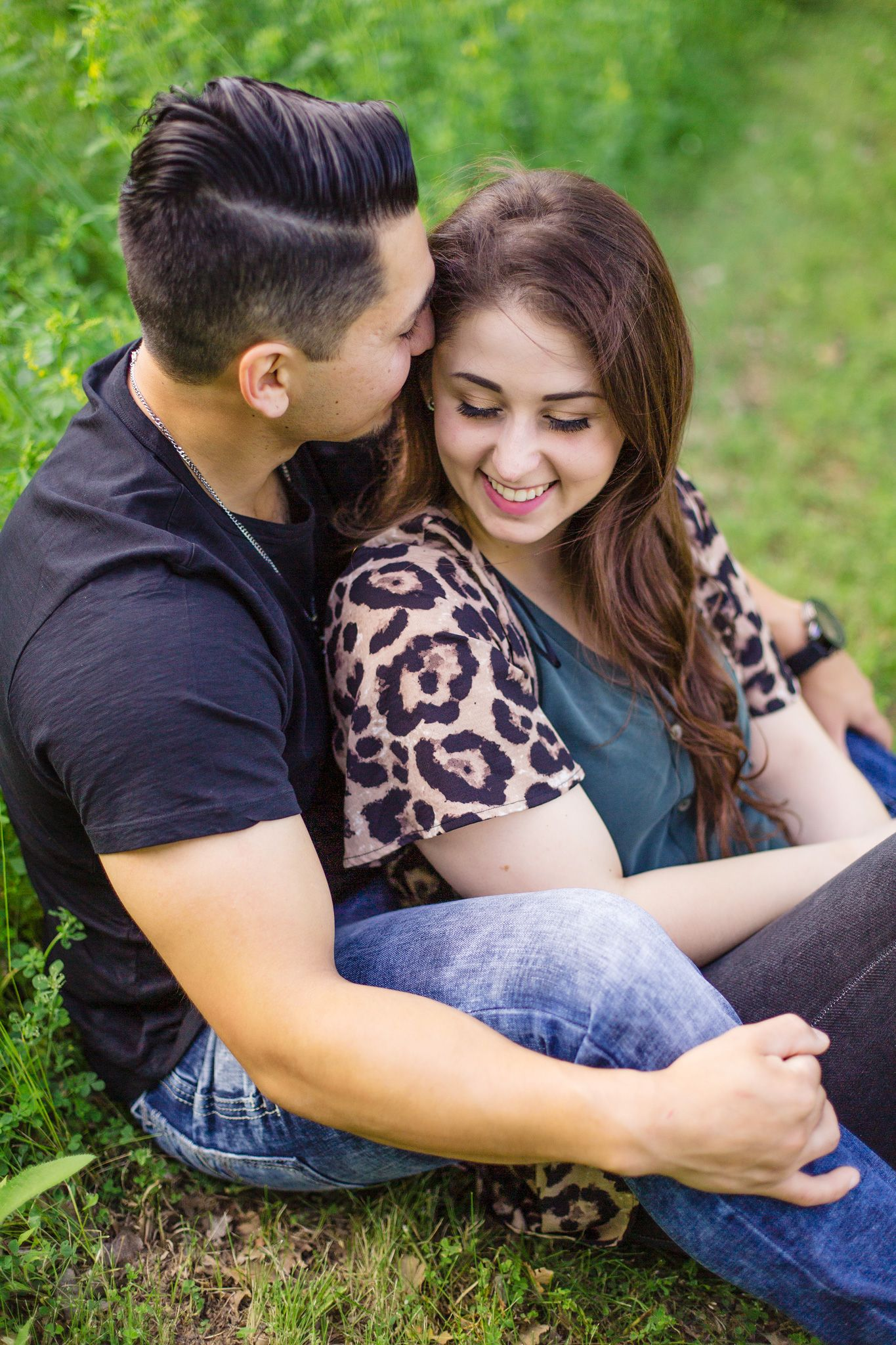 Engagement photo of a couple snuggling in the grass at Mahoney State Park