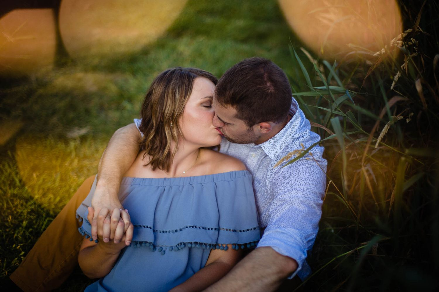 A couple kissing in the grass at Chalco Hills Recreation Area