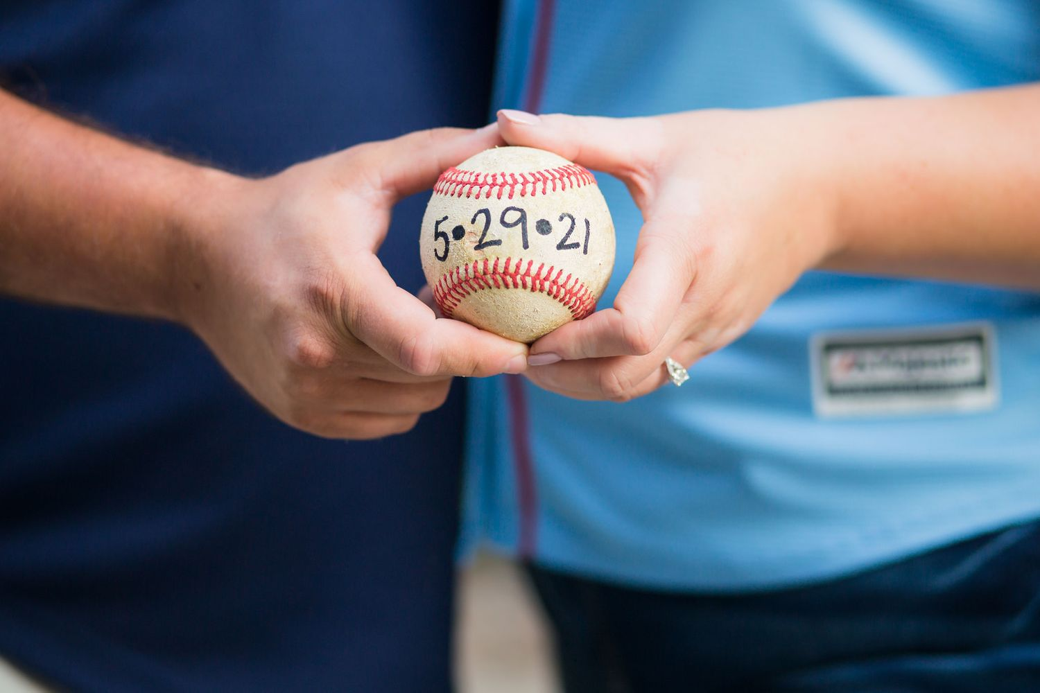 Omaha couple holds a baseball with their wedding date written on it.