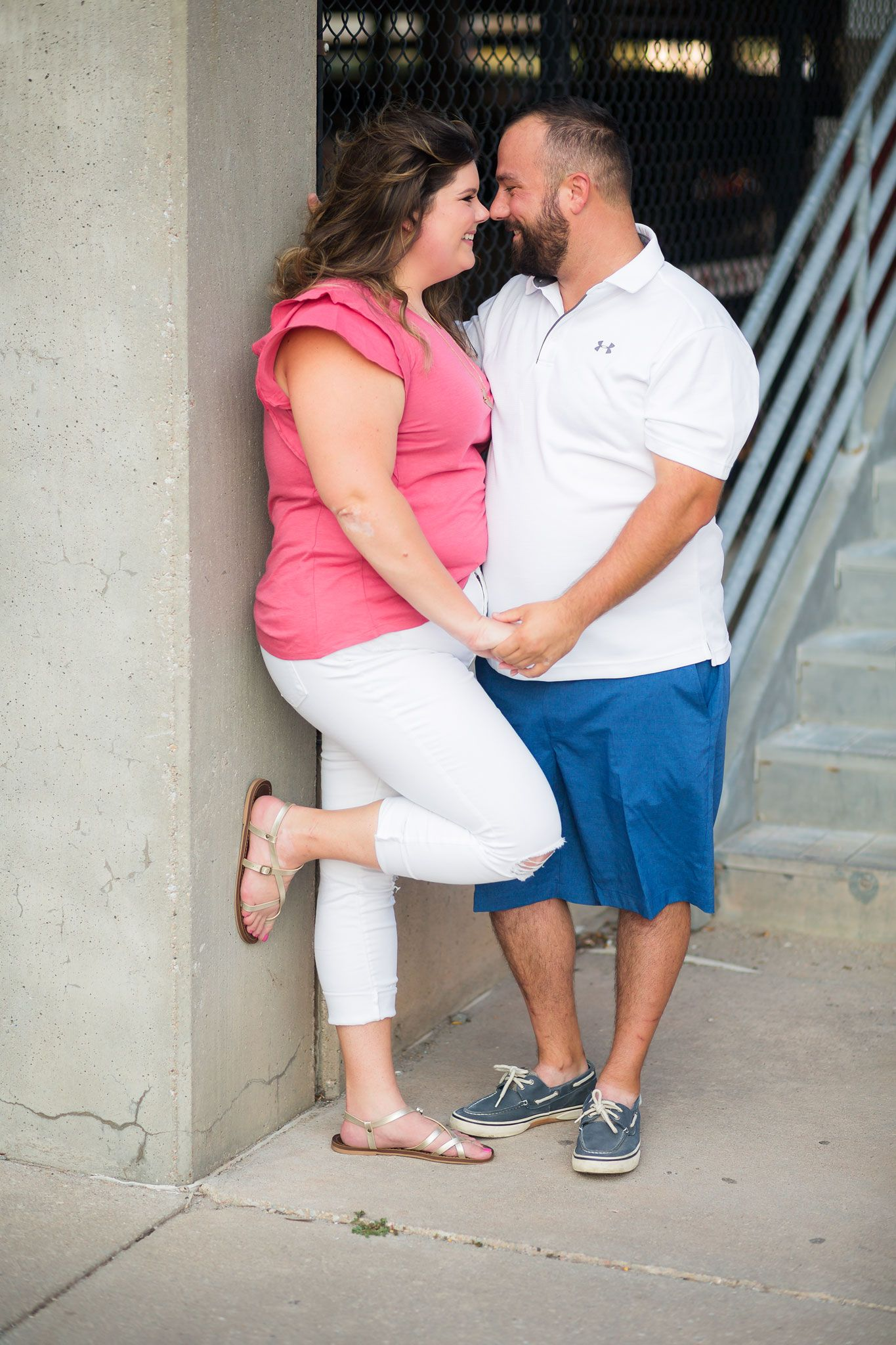 Engaged couple poses alongside a parking garage in downtown Omaha.