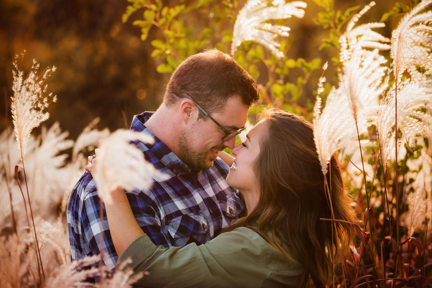 Fall portrait of a couple embracing in a sunlit field.