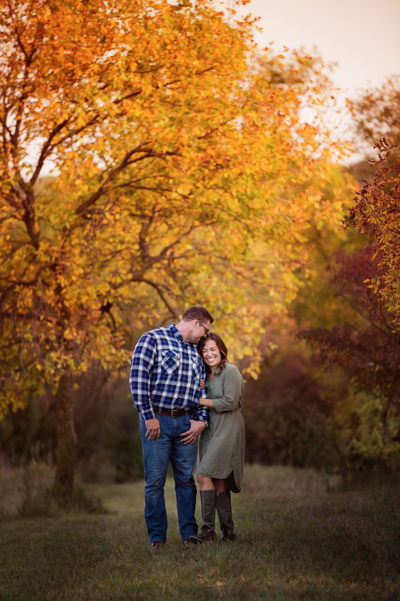 Omaha photography of a couple snuggled up under a tree full of fall leaves.