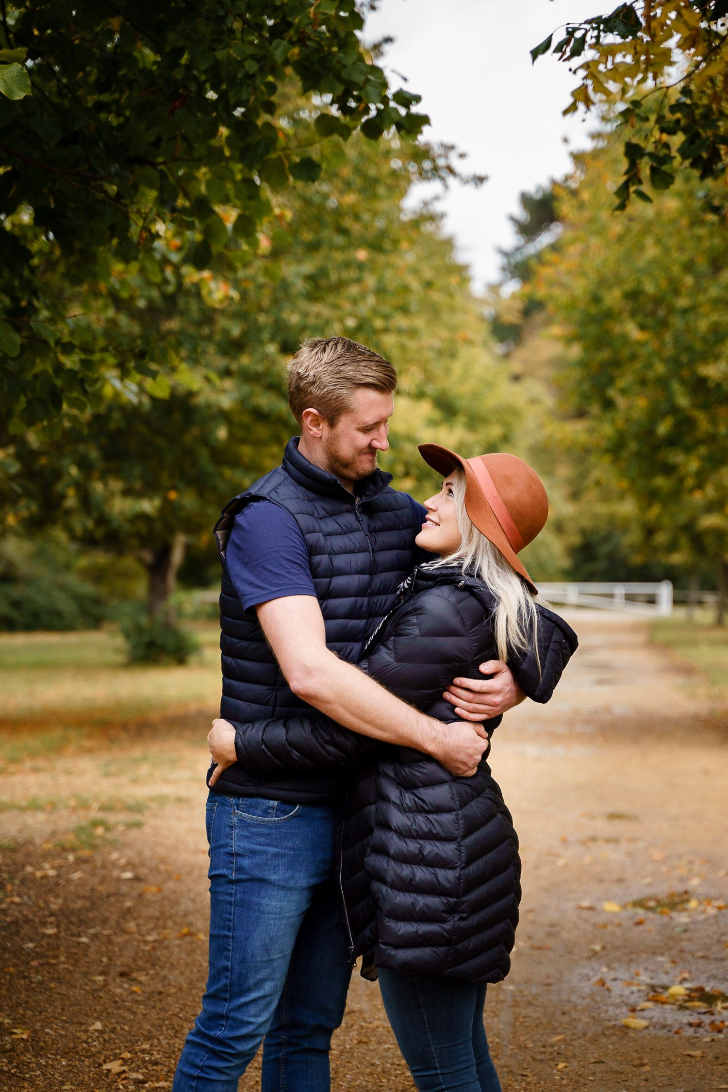 A heterosexual couple cuddle in a local park in autumn. Katherine and her Camera engagement photoshoot.