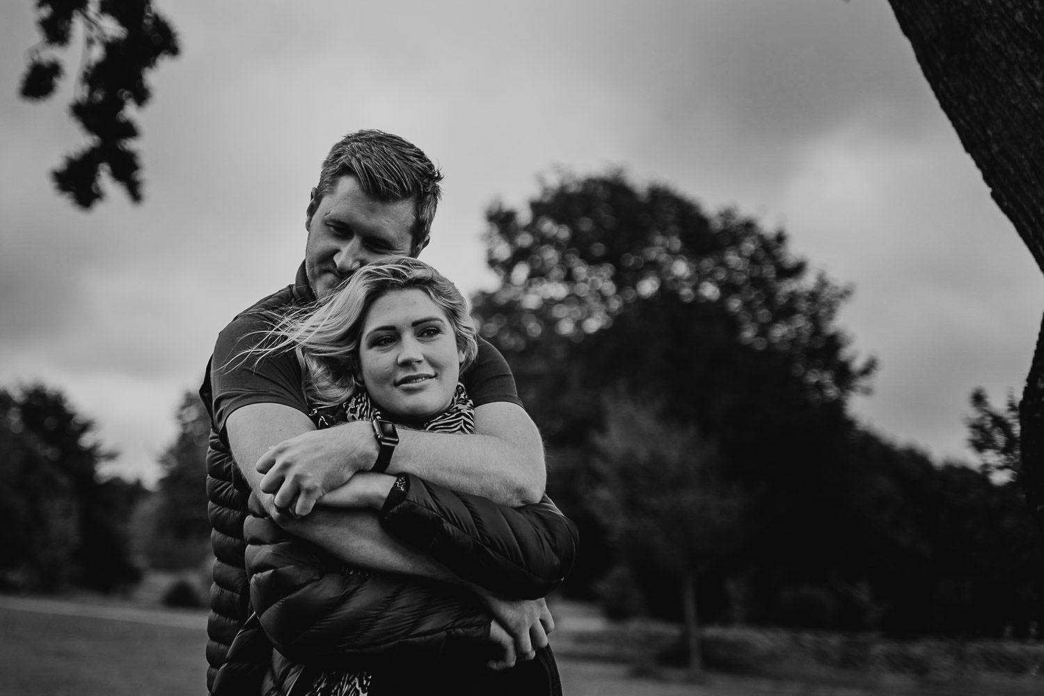 Black and white image of a couple sharing a moment and cuddle in a park. Katherine and her Camera engagement photoshoot.