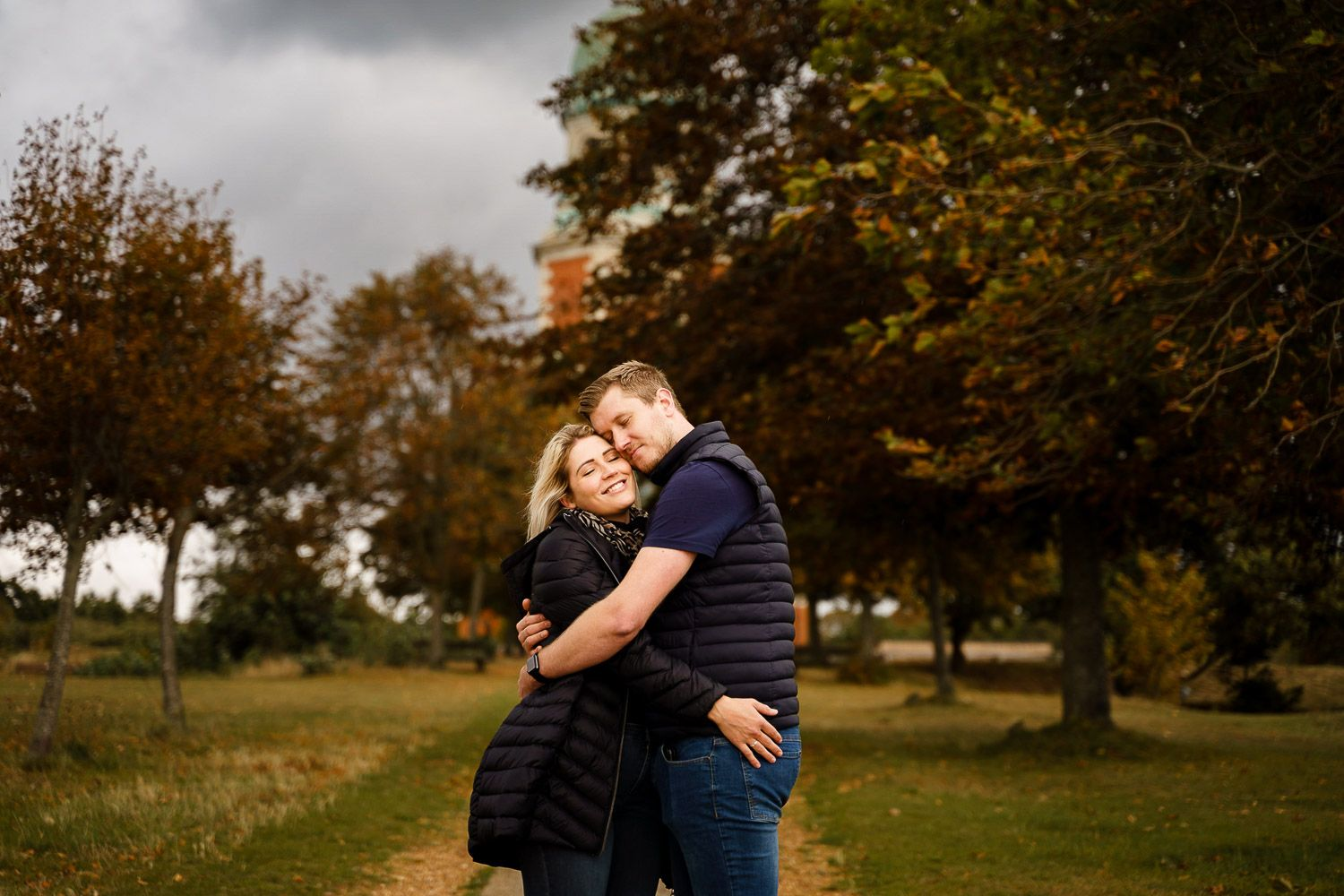 Couple have a cuddle and look out to sea in front of Netley Chapel. Katherine and her Camera engagement photoshoot.