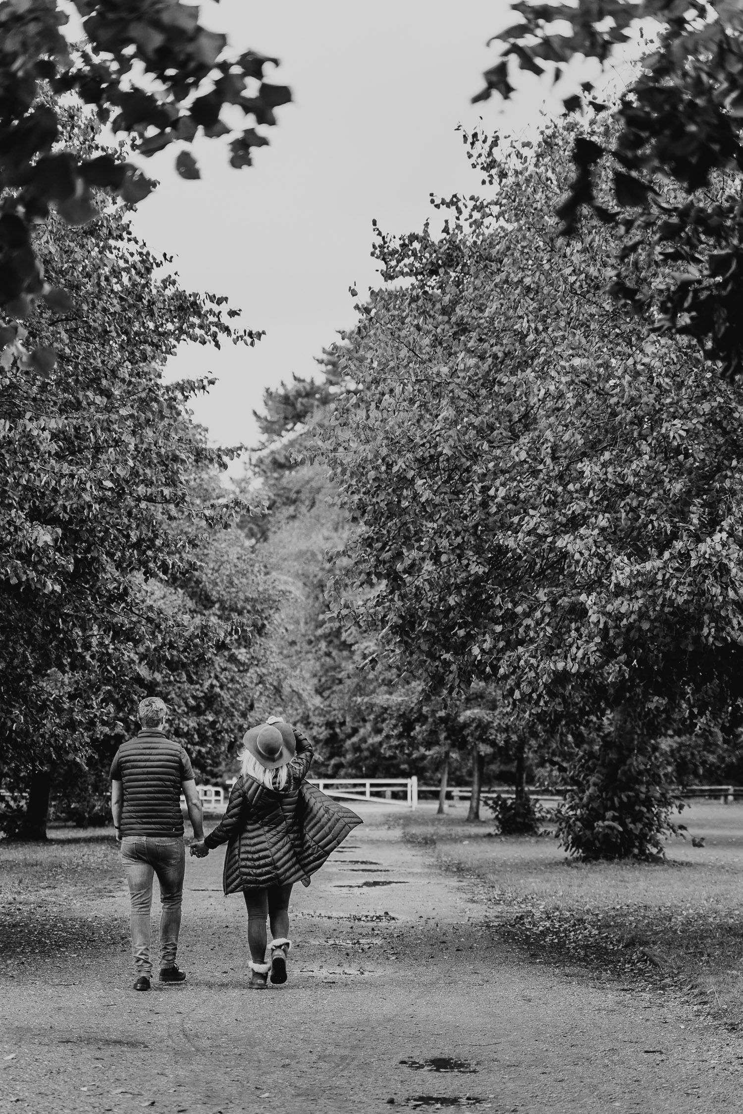 Black and white image of a couple walking away down a park path. Katherine and her Camera engagement photoshoot.