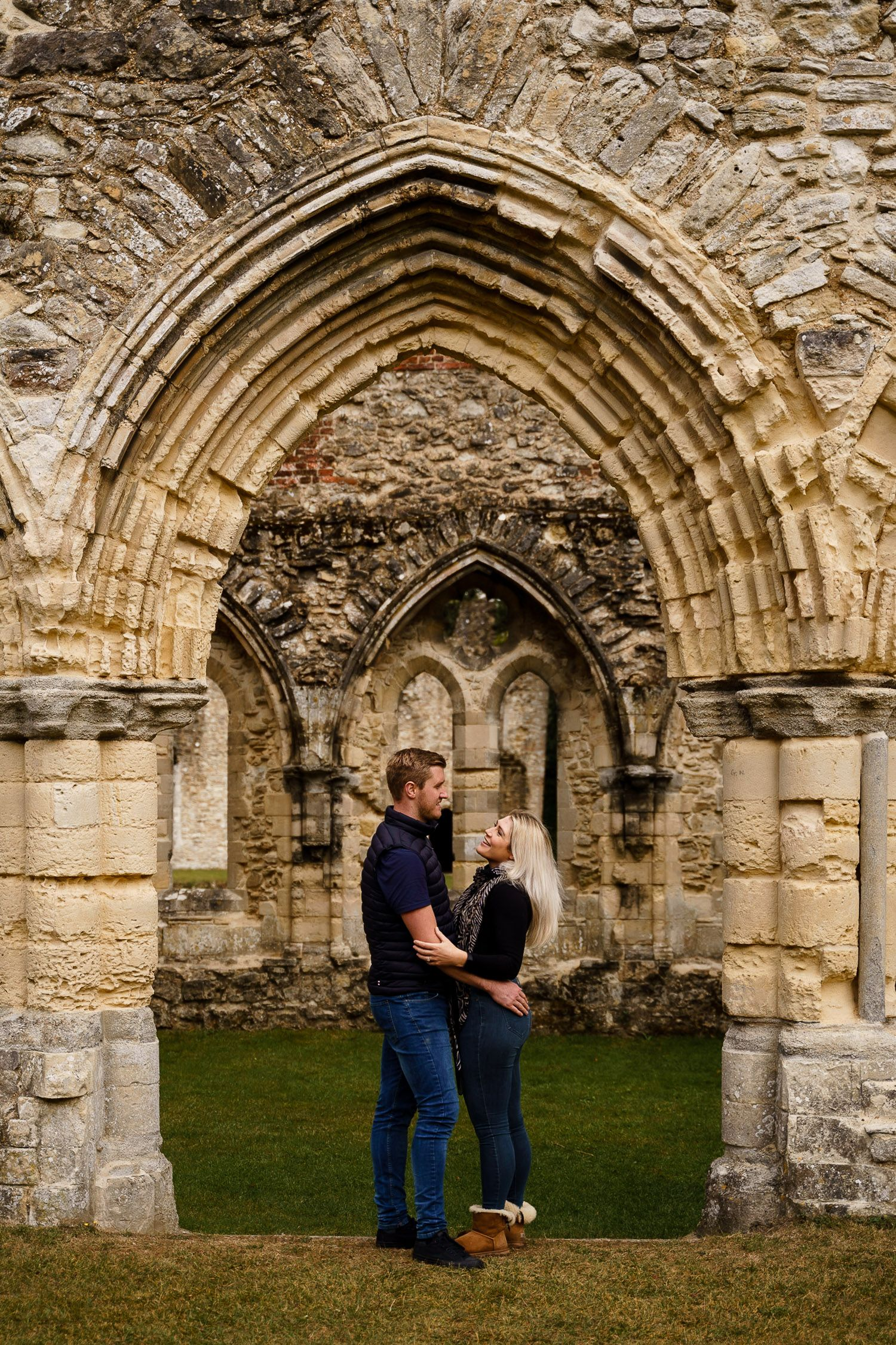 Portrait of couple laughing together framed by an arch in Netley Abbey. Katherine and her Camera engagement photoshoot.