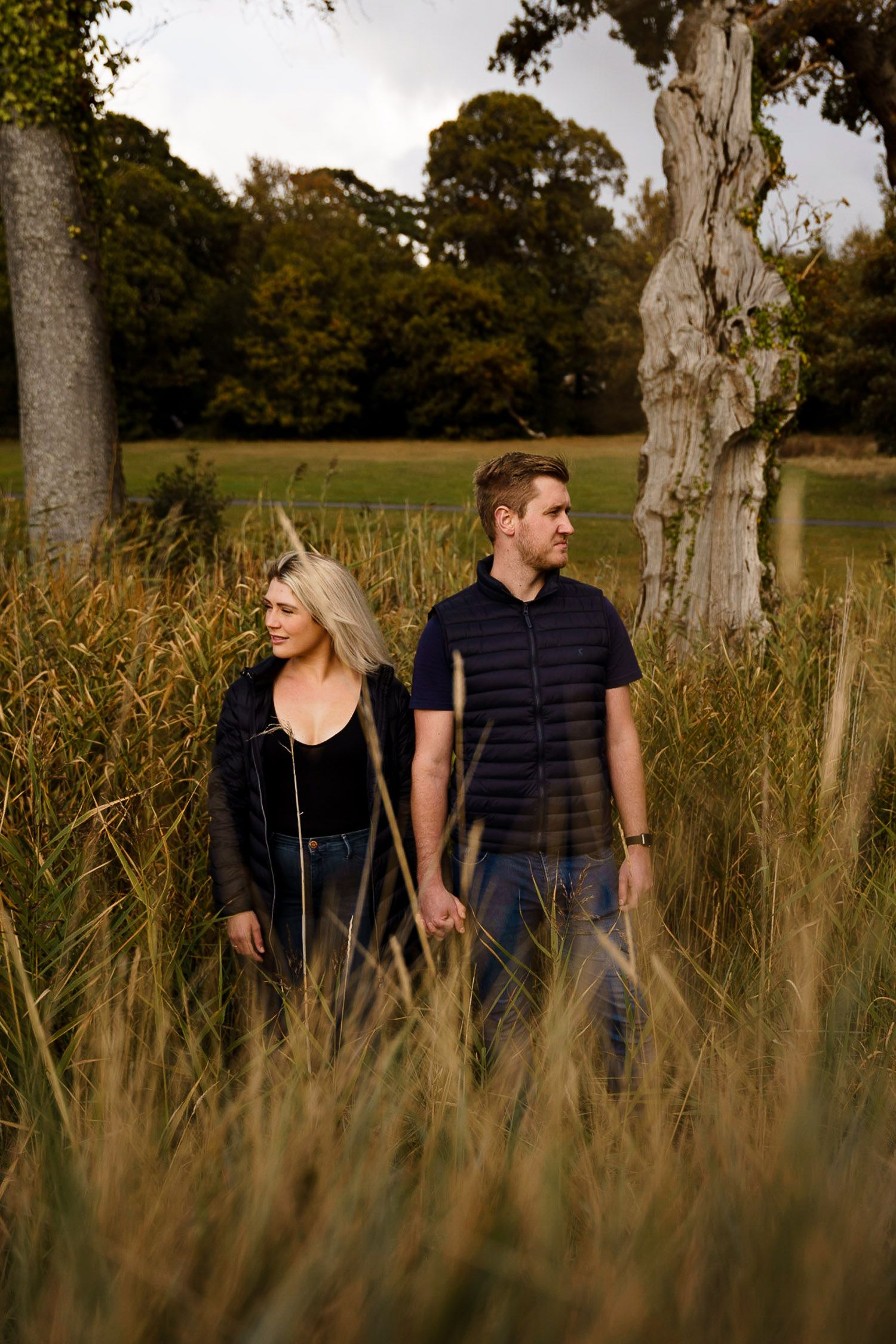 Couple stand in tall grass holding hands and looking in opposite directions. Katherine and her Camera