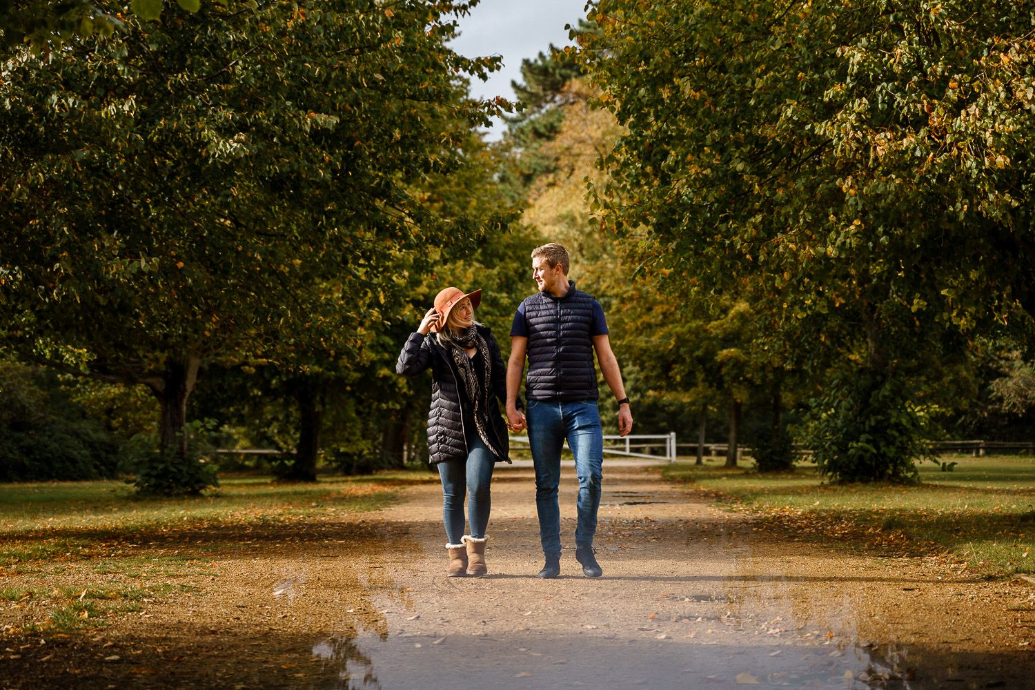 Couple walk towards the camera holding hands in an autumnal park. Katherine and her Camera engagement photoshoot.