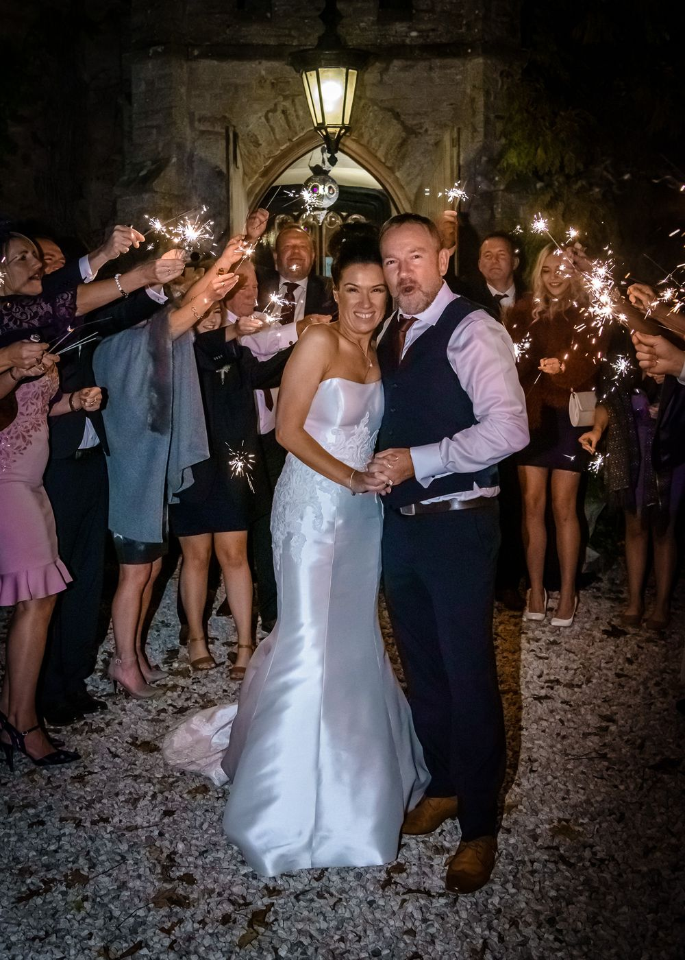 Bride and groom surrounded by quests with sparklers
