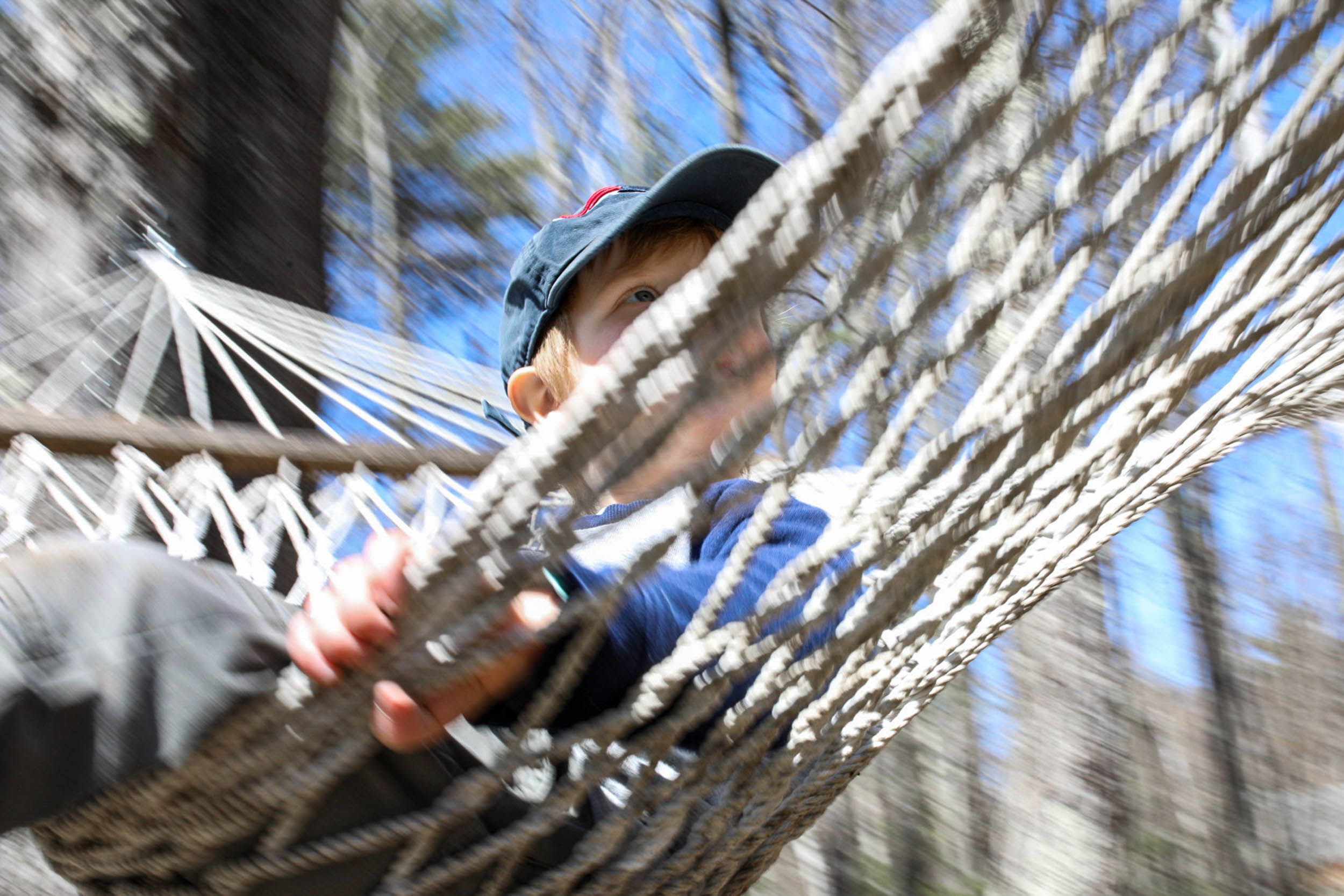 Boy wearing a baseball hat swinging in a hammock under blue skies in Alton New Hampshire during spring