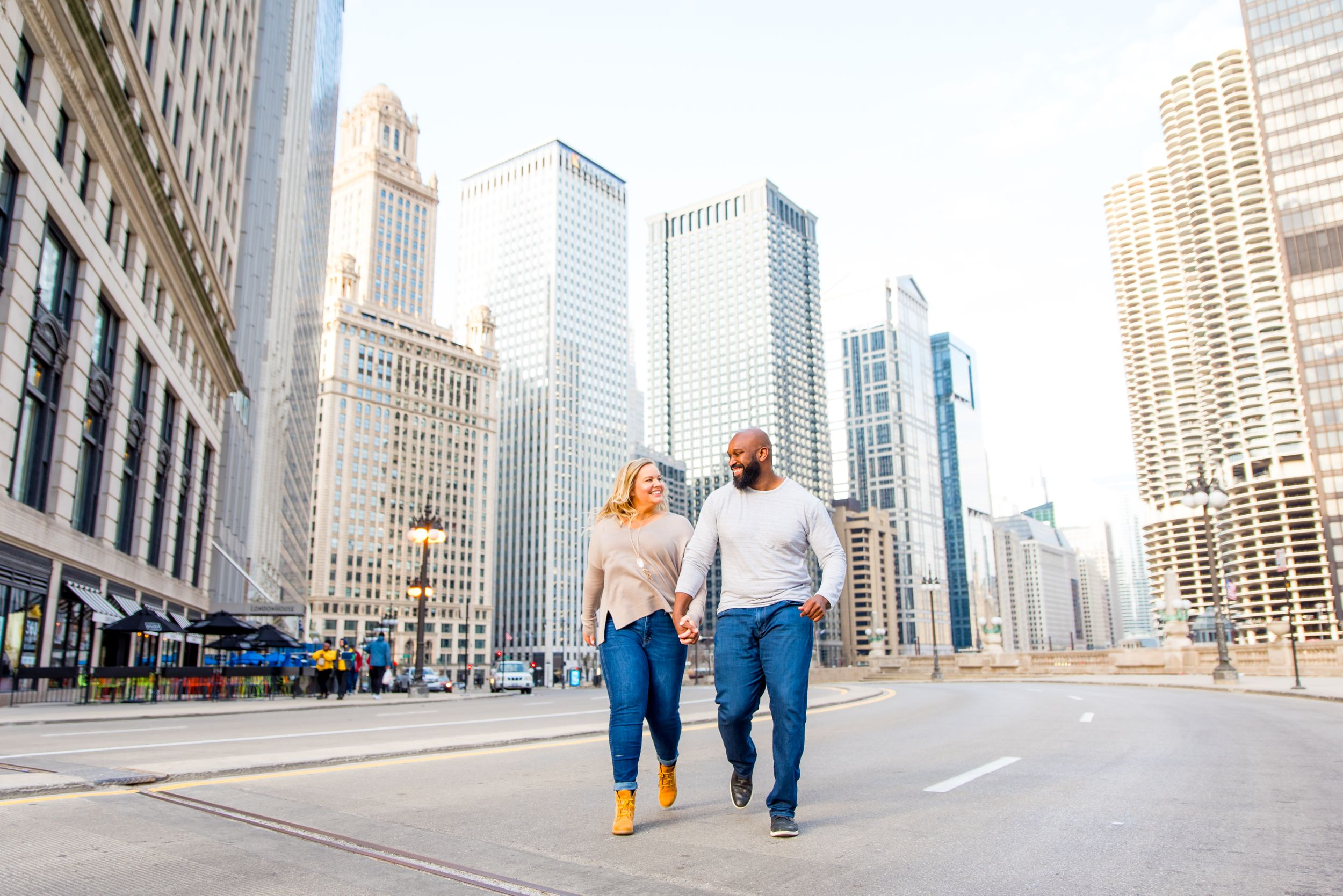man and woman holding hands smiling running through Michigan Ave for Chicago engagement photos