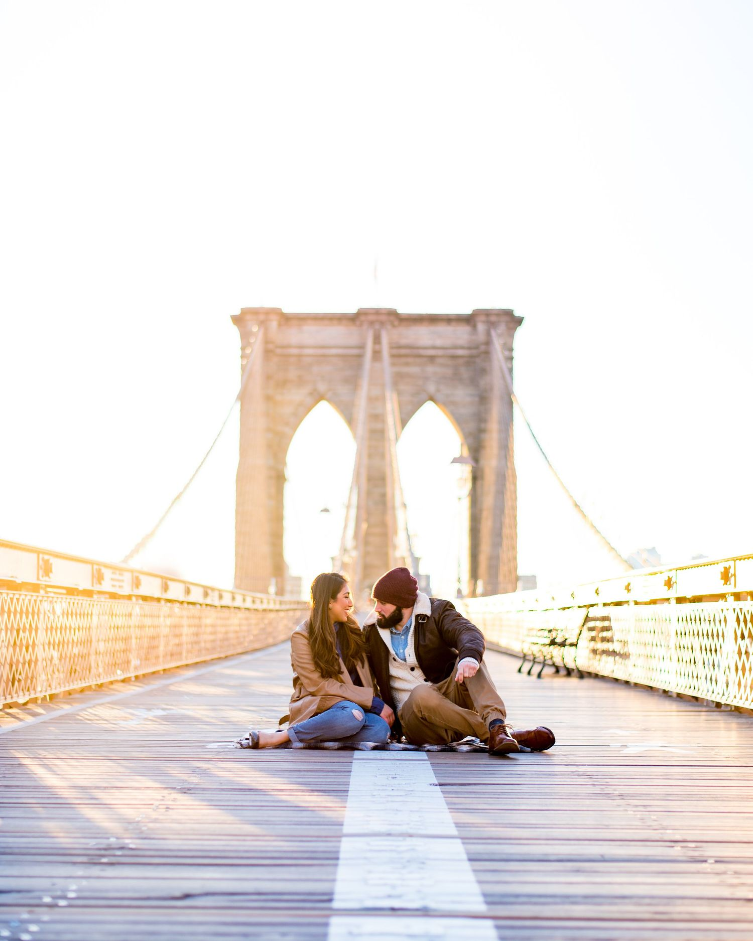 engaged couple sitting in the middle of an empty Brooklyn Bridge at sunrise in NYC while laughing and cuddling