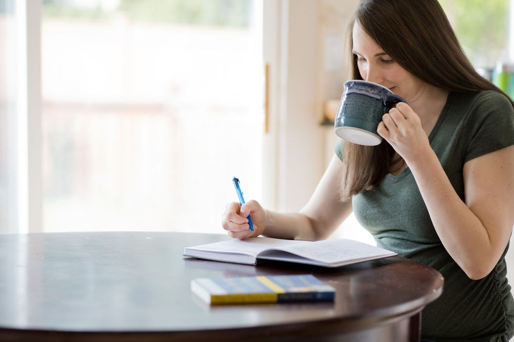 woman business owner drinking lemon water while working on business planning