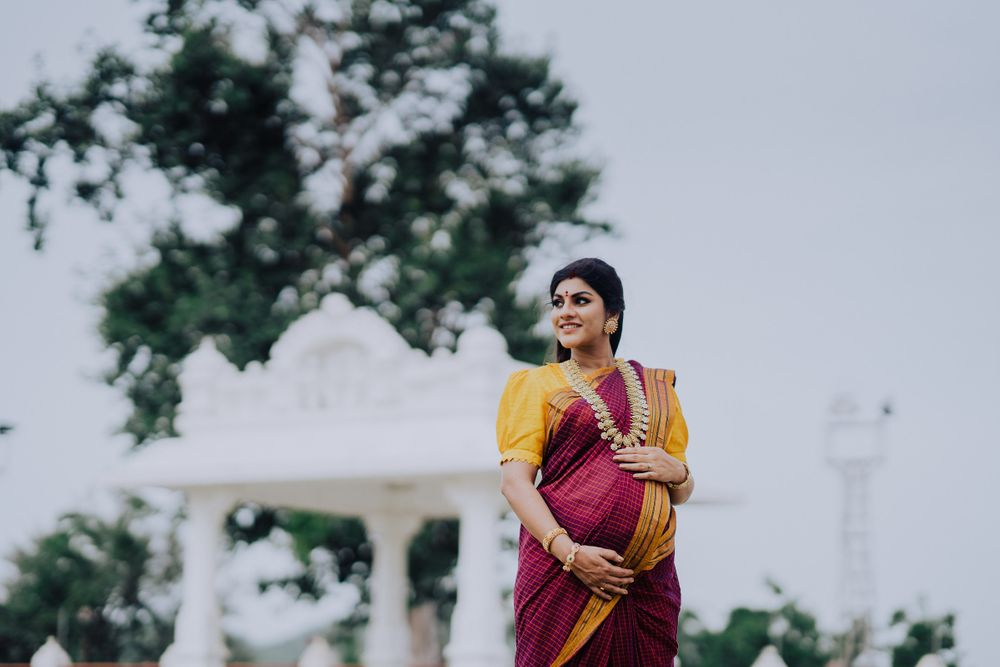 Beautifully smiling pregnant woman holding her maternity belly, maternity photoshoot indian style